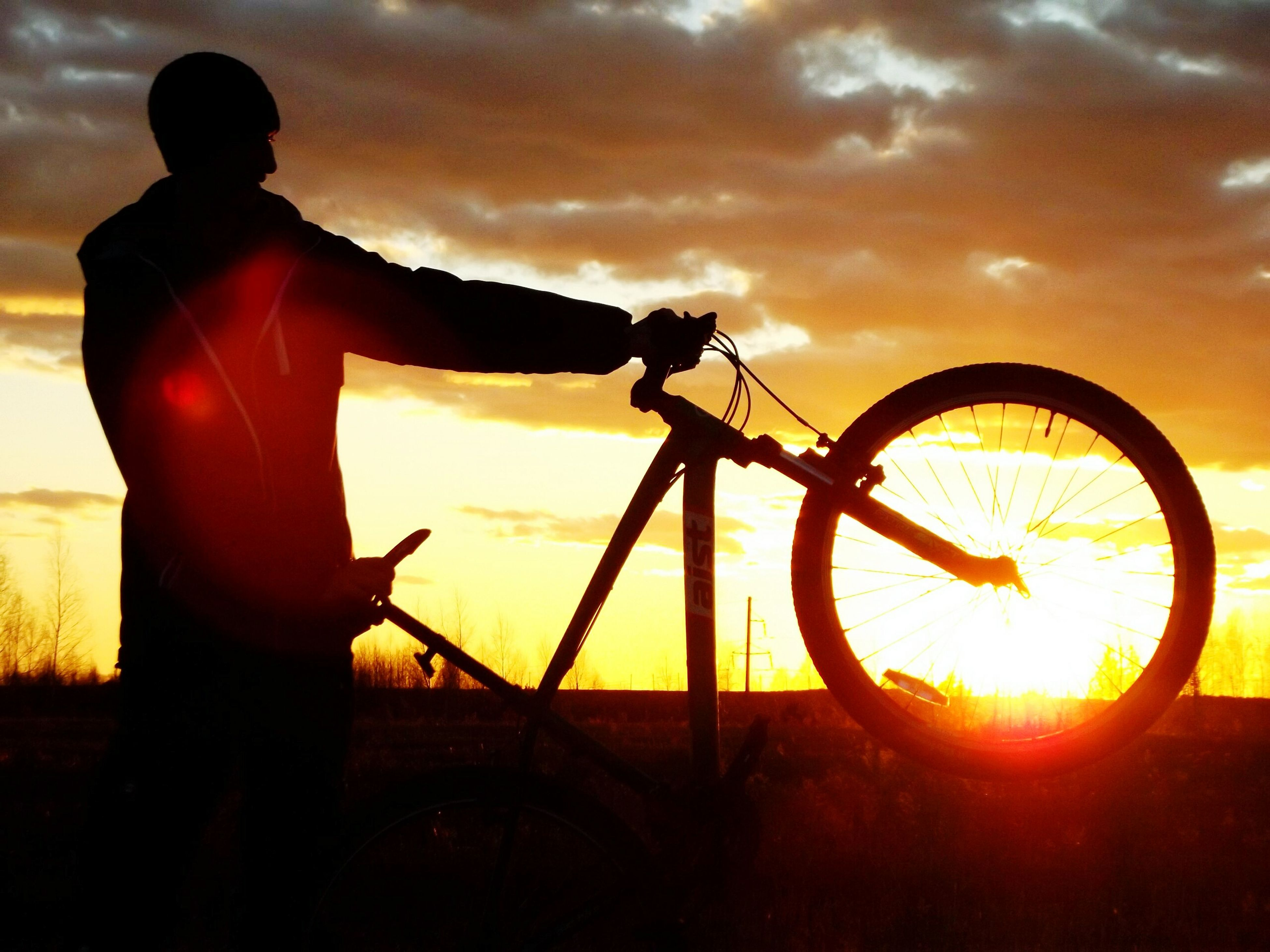 bicycle, cycling, sunset, sky, land vehicle, one person, silhouette, outdoors, tire, men, nature, headwear, spoke, people