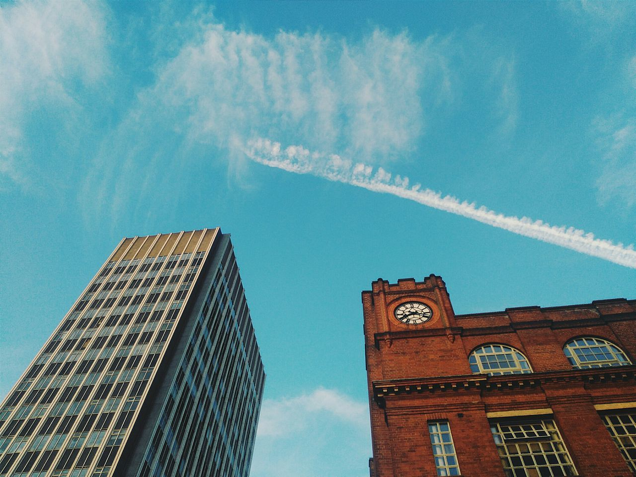 low angle view, architecture, building exterior, built structure, sky, day, cloud - sky, outdoors, no people, vapor trail
