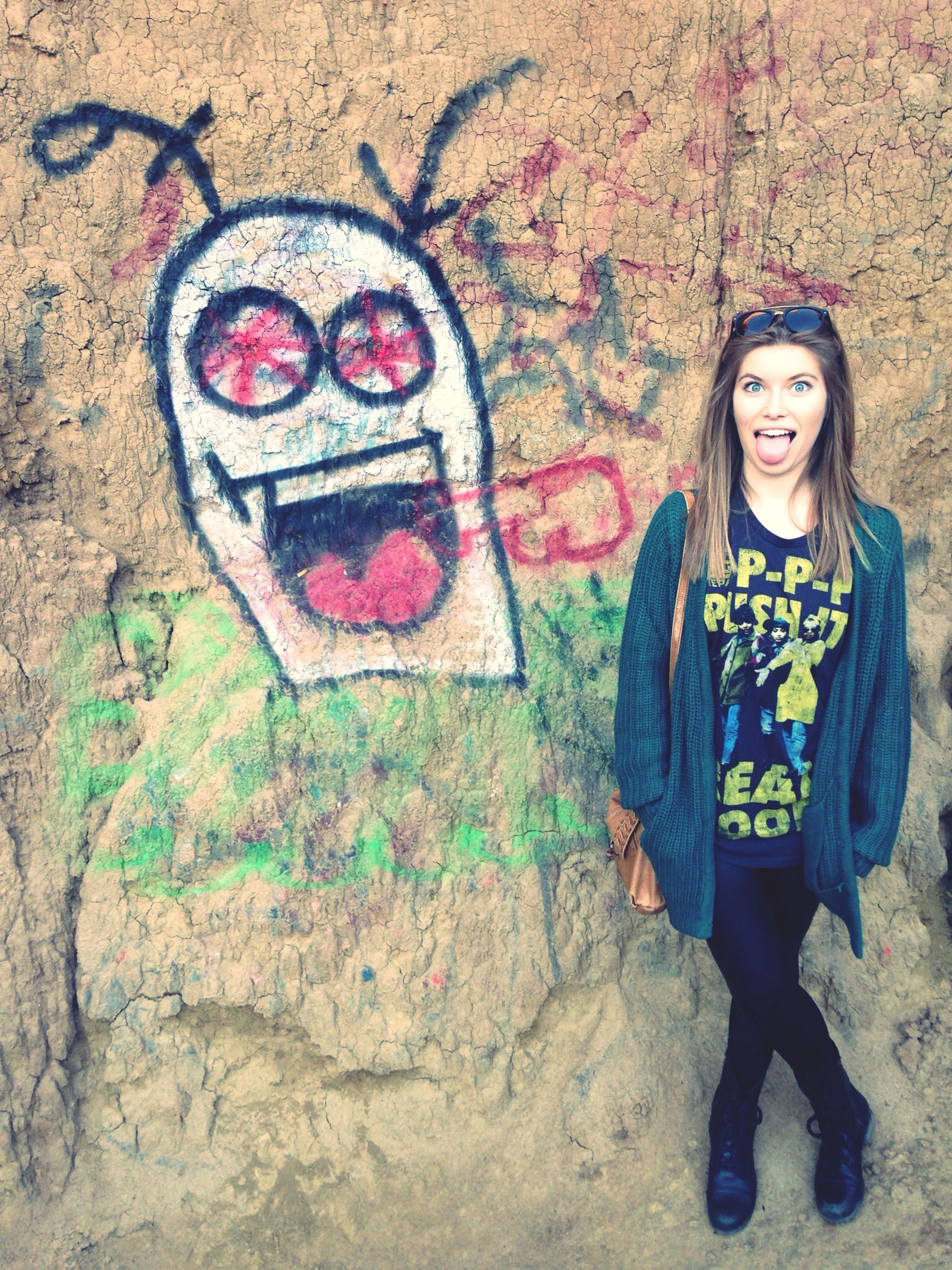 lifestyles, person, casual clothing, leisure activity, young adult, wall - building feature, standing, young women, full length, portrait, front view, looking at camera, graffiti, smiling, happiness, three quarter length, day, outdoors