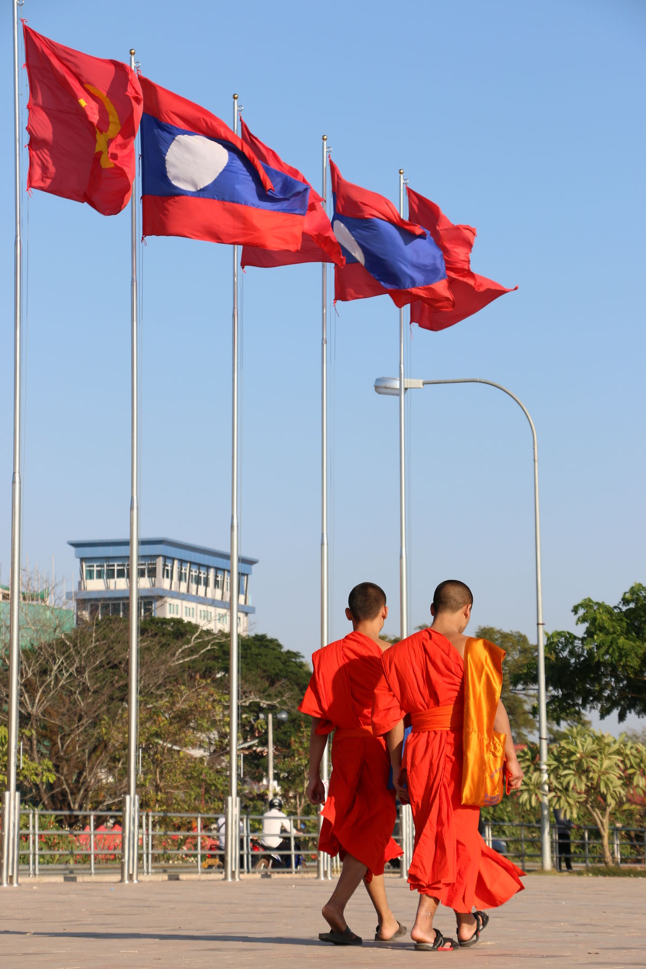 Mekong promenade Blue Sky Buddist Buddist Monk Culture Flag Flags Flags In The Wind  Laos Mekong Promenade Mekong River Monks Monks Walk Outdoors Promenade Religion Summer Travel Travel Photography Two People Vientiane Walking Monks