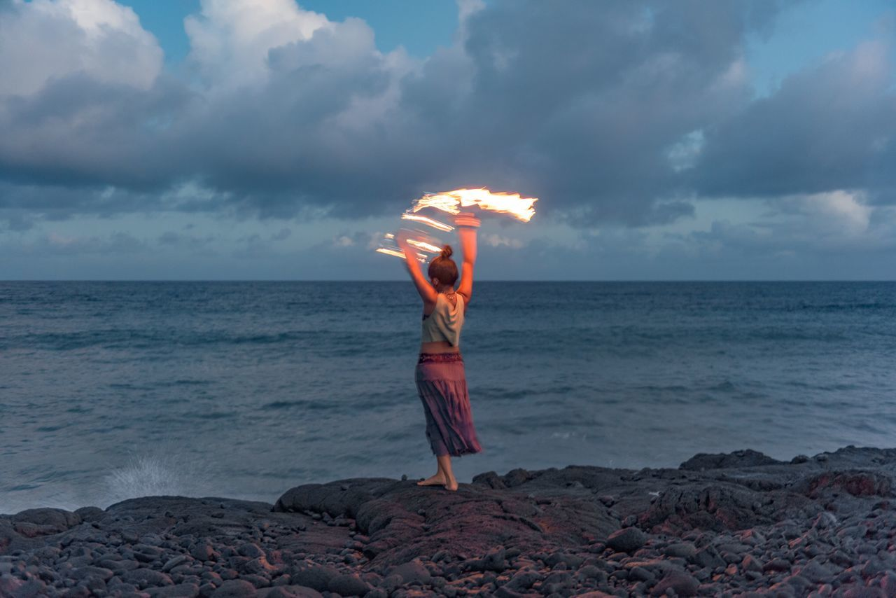 Pretty fire spinning girl, says good bye to the day in Hawaiian style. Fire Spinning Pretty Girl Pacific Ocean Sunset Unrecognisable Person Kaimu Black Sand Beach Big Island Hawaii Dancing Girl Show capturing motion Long Goodbye