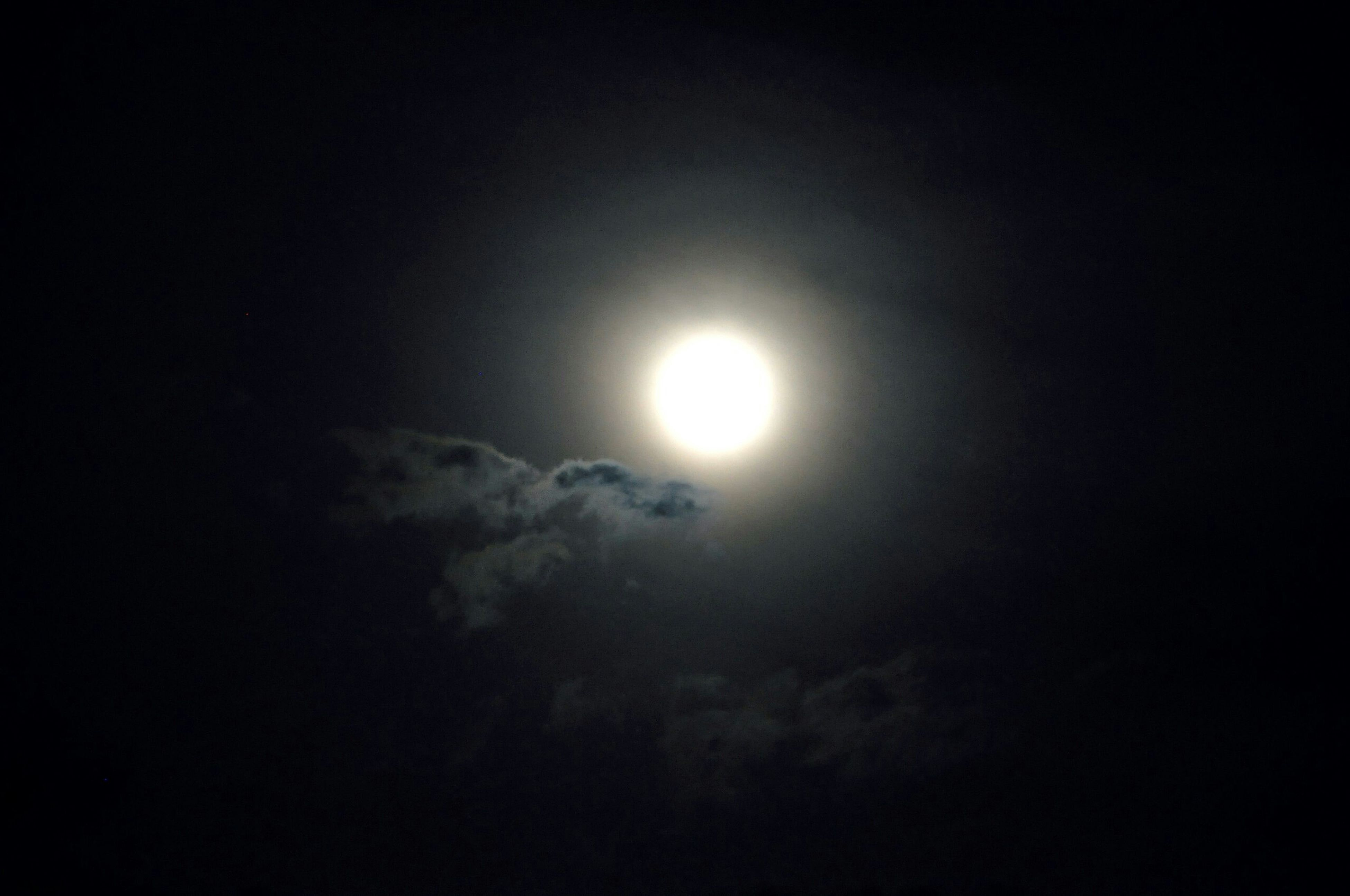 low angle view, sky, moon, sun, beauty in nature, scenics, sky only, tranquility, nature, tranquil scene, cloud - sky, idyllic, night, outdoors, copy space, no people, dark, weather, majestic, lens flare