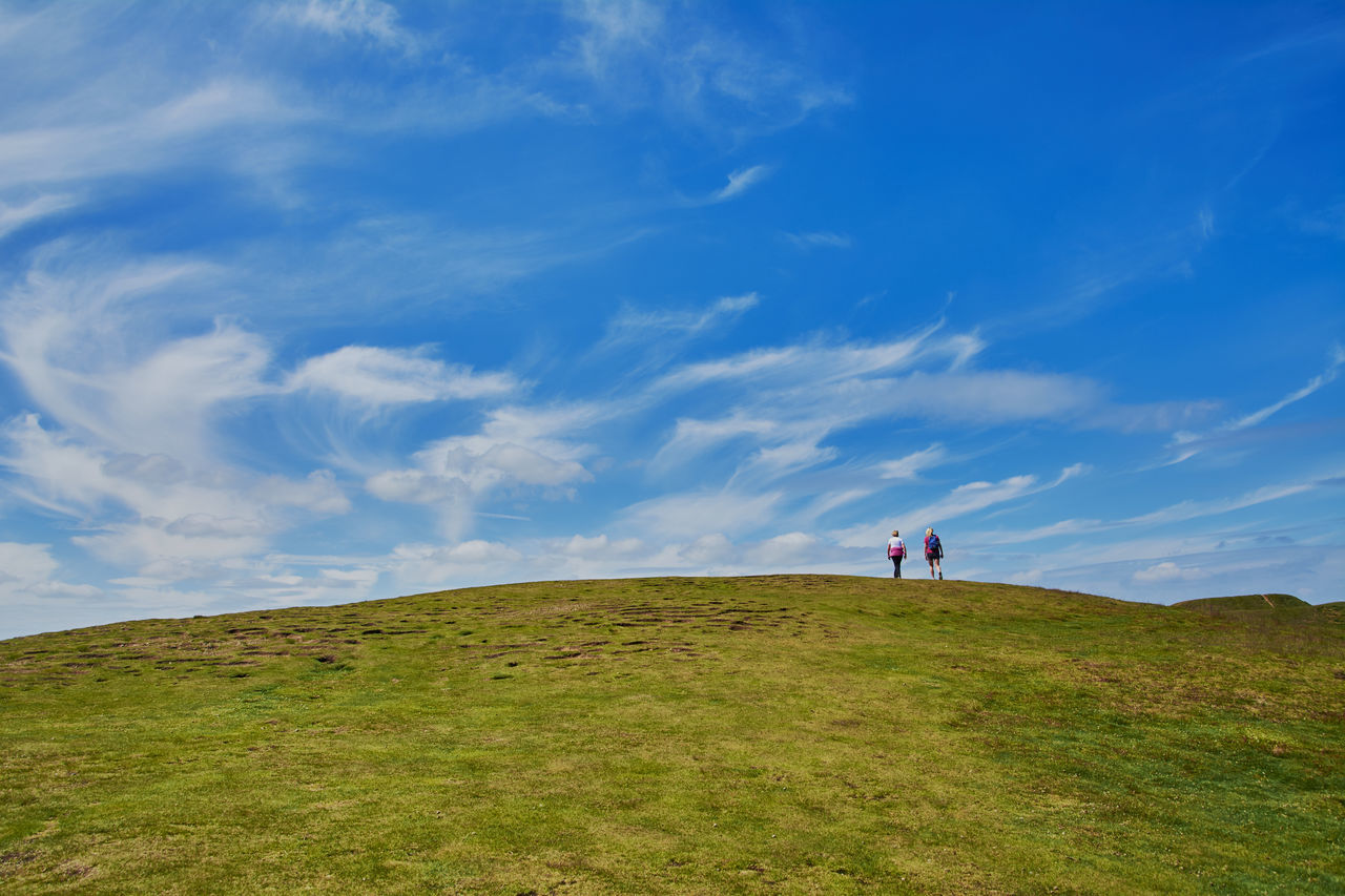 TWO DISTANT TOURISTS WALKING ON GREEN HILL