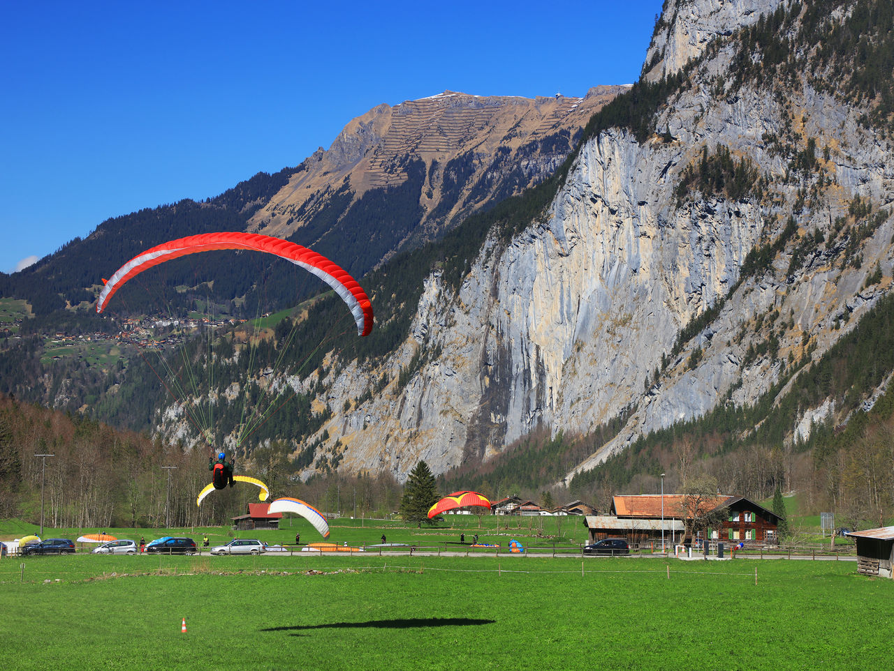 mountain, adventure, leisure activity, day, grass, nature, outdoors, extreme sports, rock - object, scenics, real people, mountain range, landscape, sport, one person, sky, parachute, lifestyles, built structure, tree, beauty in nature, tent, multi colored, architecture, clear sky, full length, paragliding, people