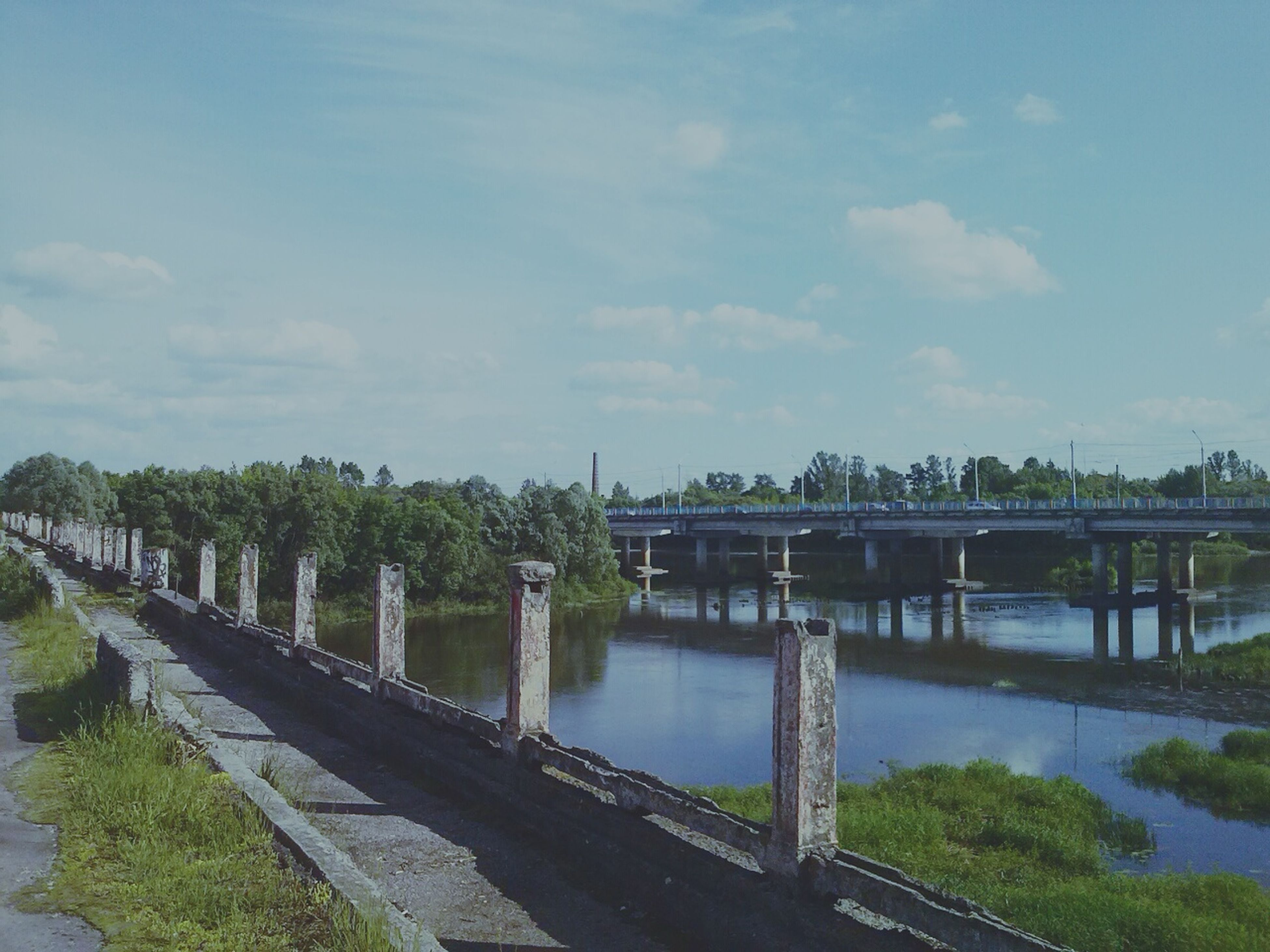 water, bridge - man made structure, connection, river, sky, built structure, railing, tree, architecture, bridge, reflection, tranquility, nature, footbridge, tranquil scene, cloud - sky, transportation, lake, day, canal