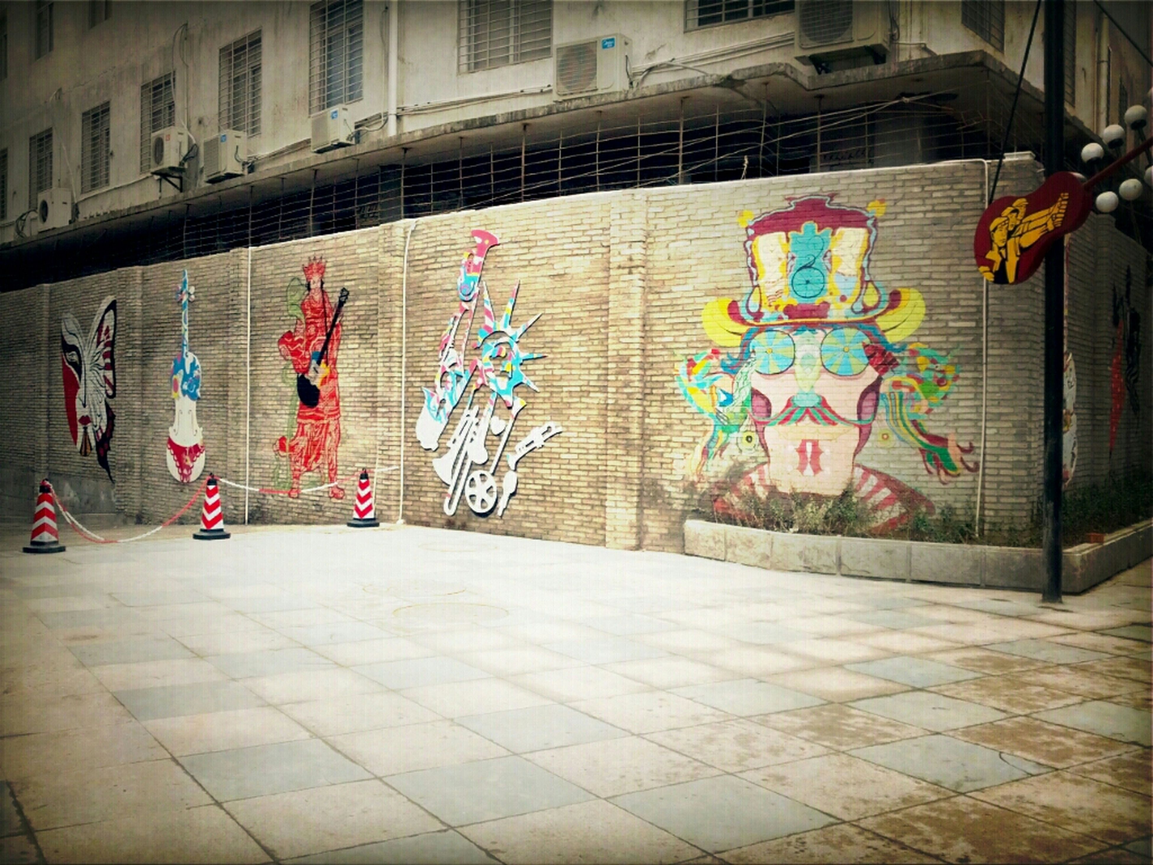 art, art and craft, creativity, graffiti, built structure, architecture, wall - building feature, text, multi colored, building exterior, western script, tiled floor, sidewalk, design, human representation, decoration, pattern, cobblestone, street art, flooring