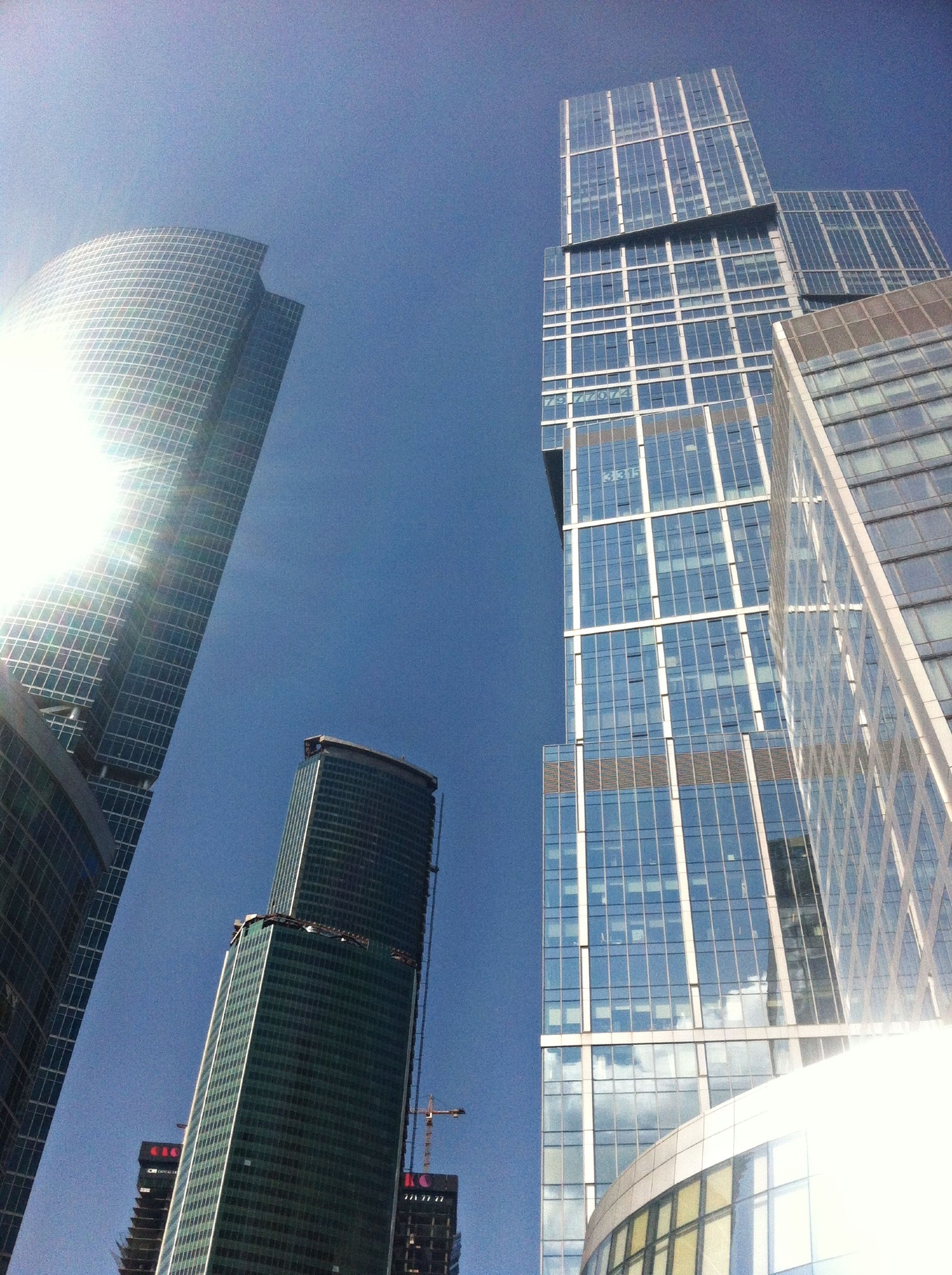 architecture, building exterior, skyscraper, modern, built structure, low angle view, tall - high, office building, city, tower, glass - material, building, financial district, sky, reflection, capital cities, development, clear sky, tall, sunlight