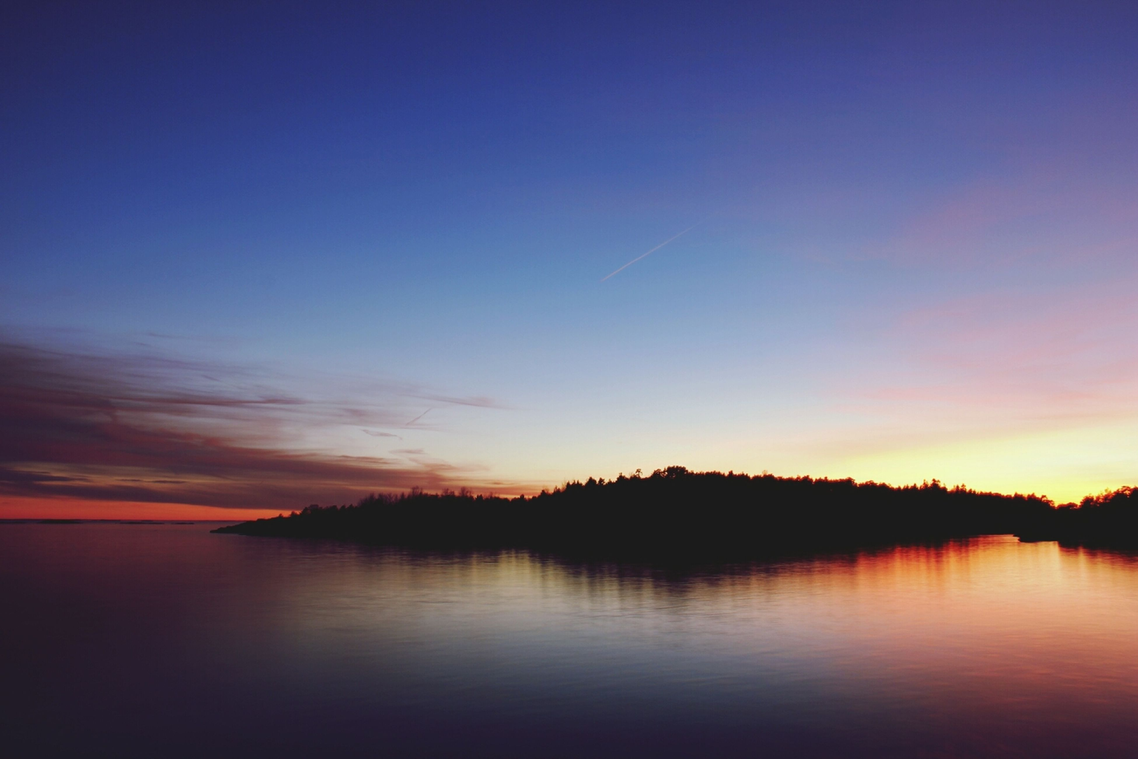 sunset, water, tranquil scene, scenics, tranquility, beauty in nature, waterfront, reflection, lake, sky, idyllic, orange color, nature, silhouette, sea, calm, copy space, dusk, blue, outdoors