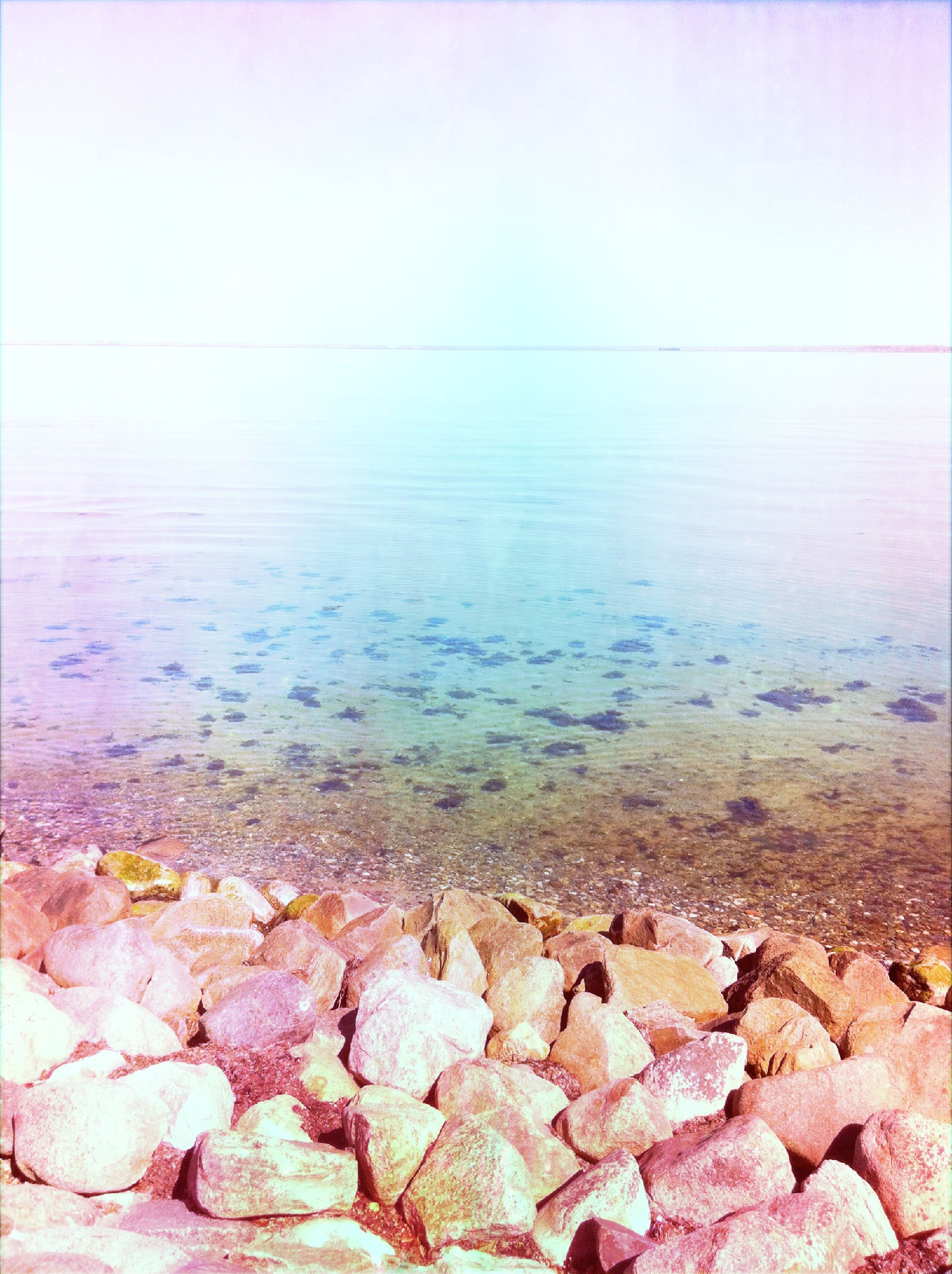 water, stone - object, tranquility, tranquil scene, nature, lake, rock - object, rippled, scenics, day, beauty in nature, outdoors, reflection, sea, stone, pebble, no people, sky, clear sky, copy space