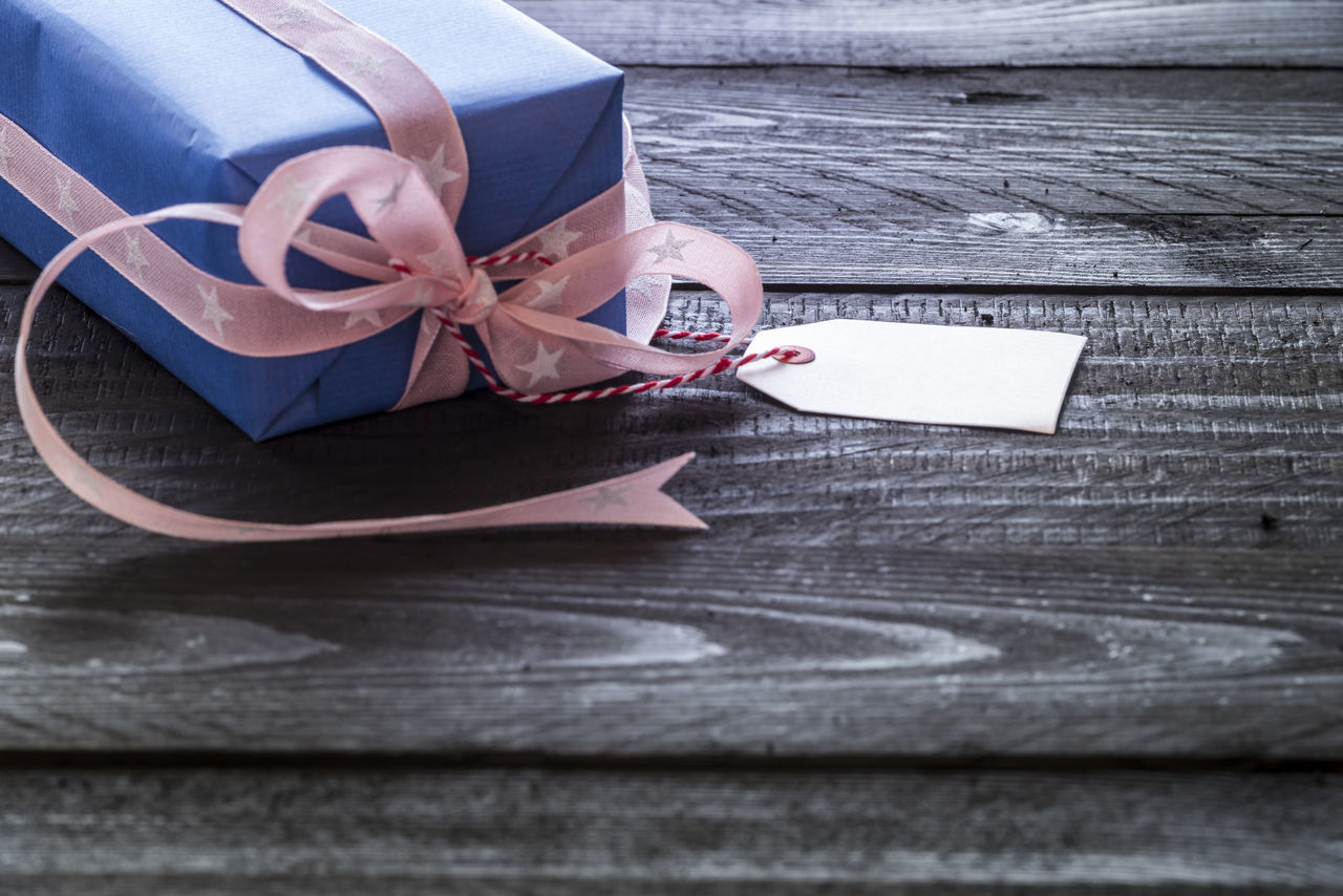 Label tag attached to gift box wrapped in blue paper tied with pink ribbon on a black wooden table Birthdaysurprise  Christmas Time Holidays Message Card Wooden Table Greeting Card  Handmade Gifts Holiday Present  Label Tag Surprise Wrapped Gift X-mas Gift