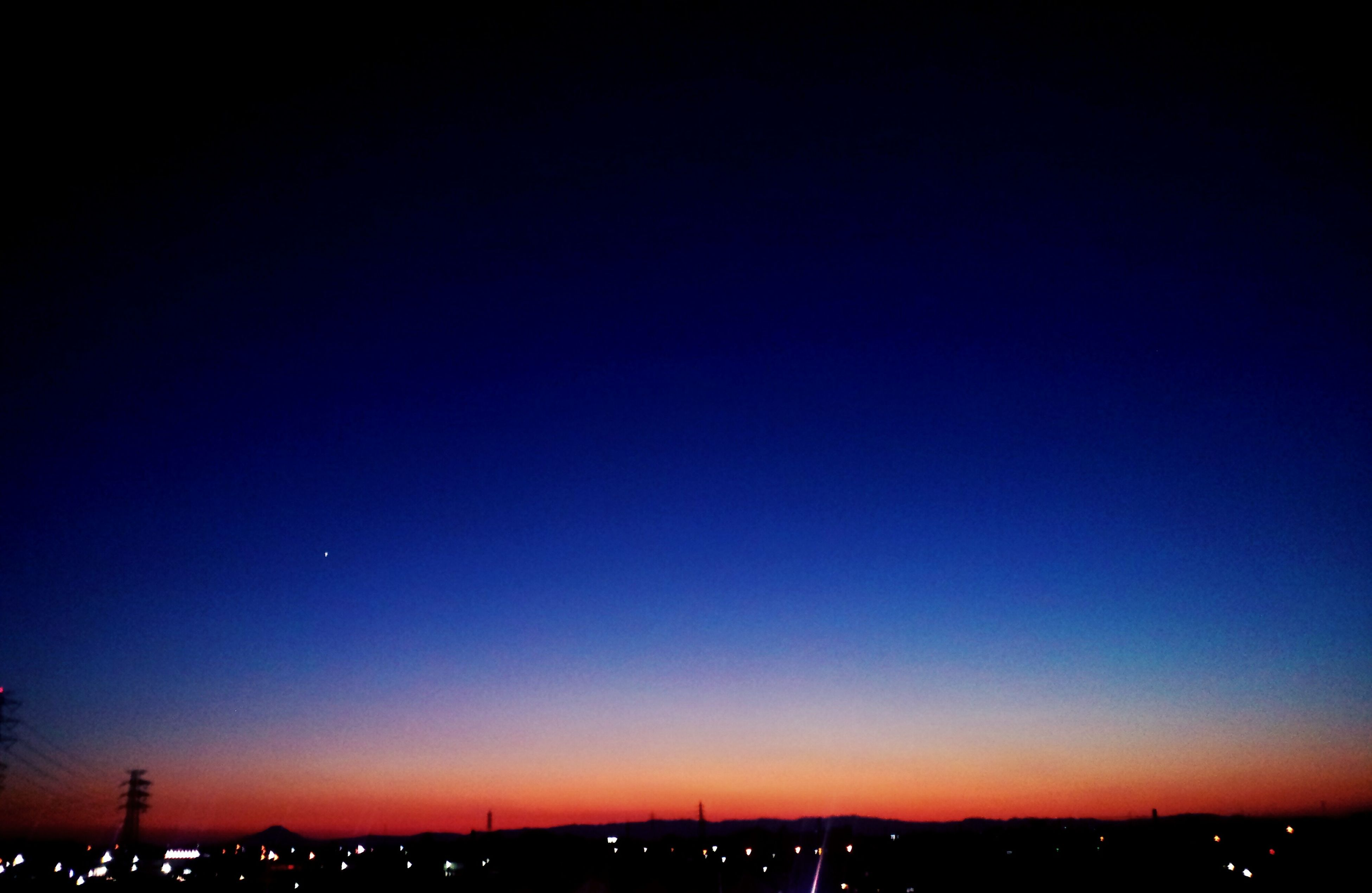 copy space, silhouette, city, illuminated, clear sky, cityscape, sunset, travel destinations, building exterior, city life, orange color, town, dark, scenics, tranquil scene, romantic sky, blue, outdoors, tourism, tranquility, high section, nature, multi colored, sky, wide shot, no people, mountain
