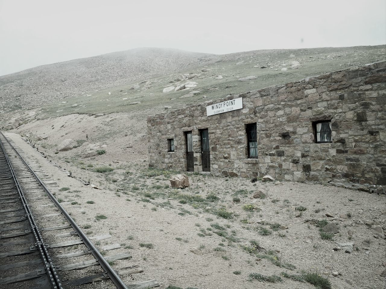 Railroad Track By Old House Against Mountain