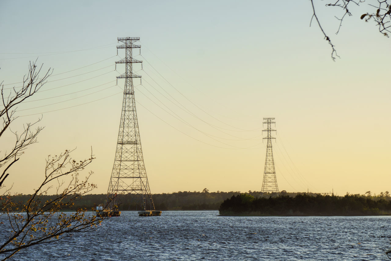 Electricity Pylon By River Against Clear Sky