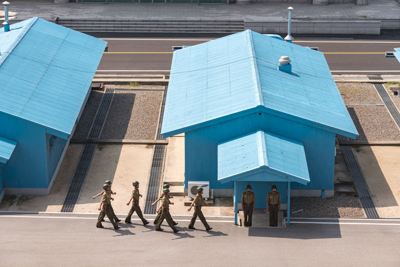 """The Joint Security Area (JSA) is the only portion of the Korean Demilitarized Zone (DMZ) where North and South Korean forces stand face-to-face. It is often called the """"Truce Village"""" in both the media. This picture was taken from the North Korea side Communism DMZ, North Korea, South Korea DPRK DPRKorea JSA Korean Korean War North Korea Soldier Army Army Soldier Blue House Building Exterior Communist Day Dmz Full Length Kaesong Seperation Standing War"""