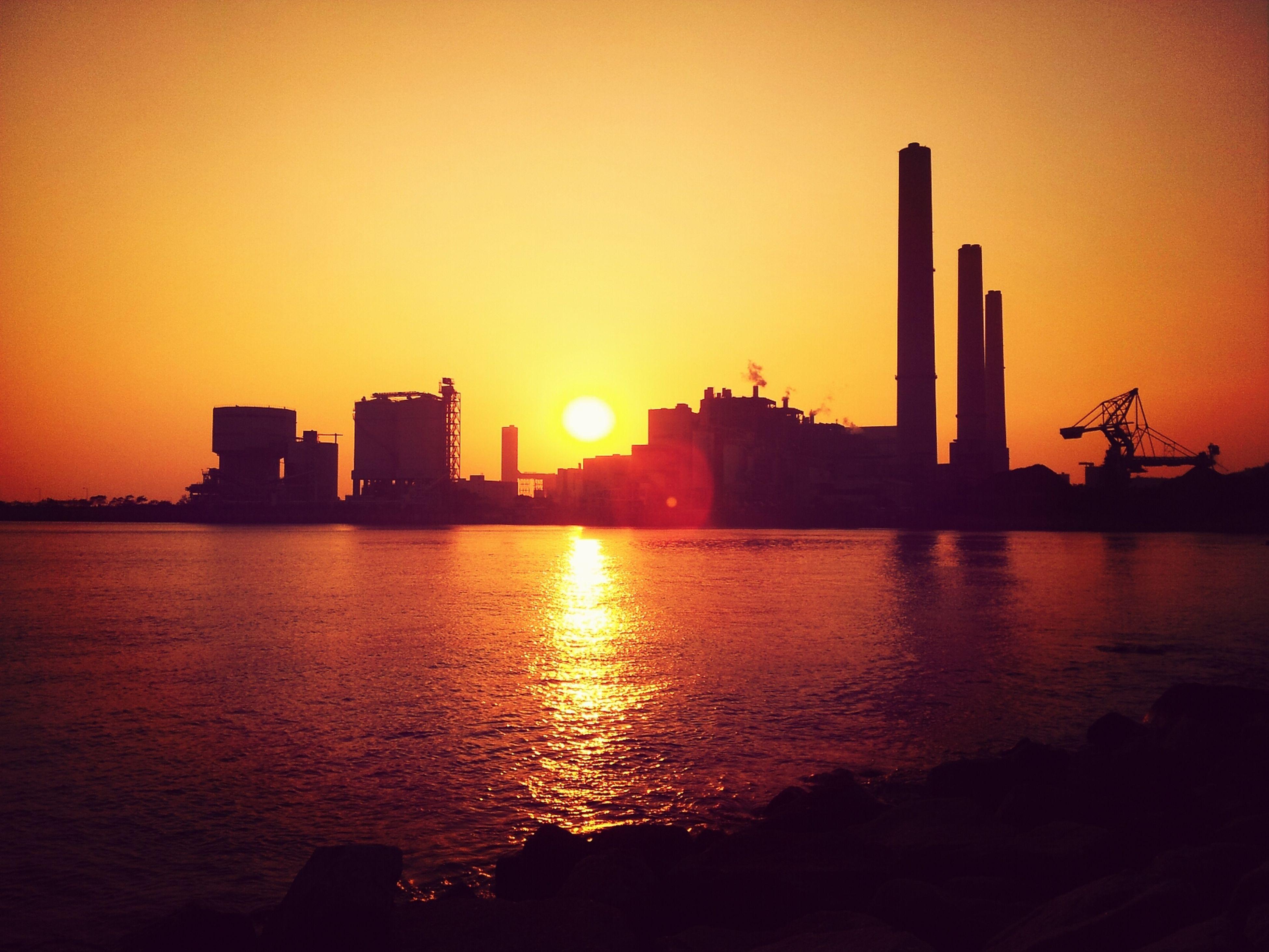 sunset, sun, architecture, building exterior, built structure, water, silhouette, orange color, city, waterfront, sea, sunlight, reflection, sky, urban skyline, tower, clear sky, development, crane - construction machinery, skyscraper