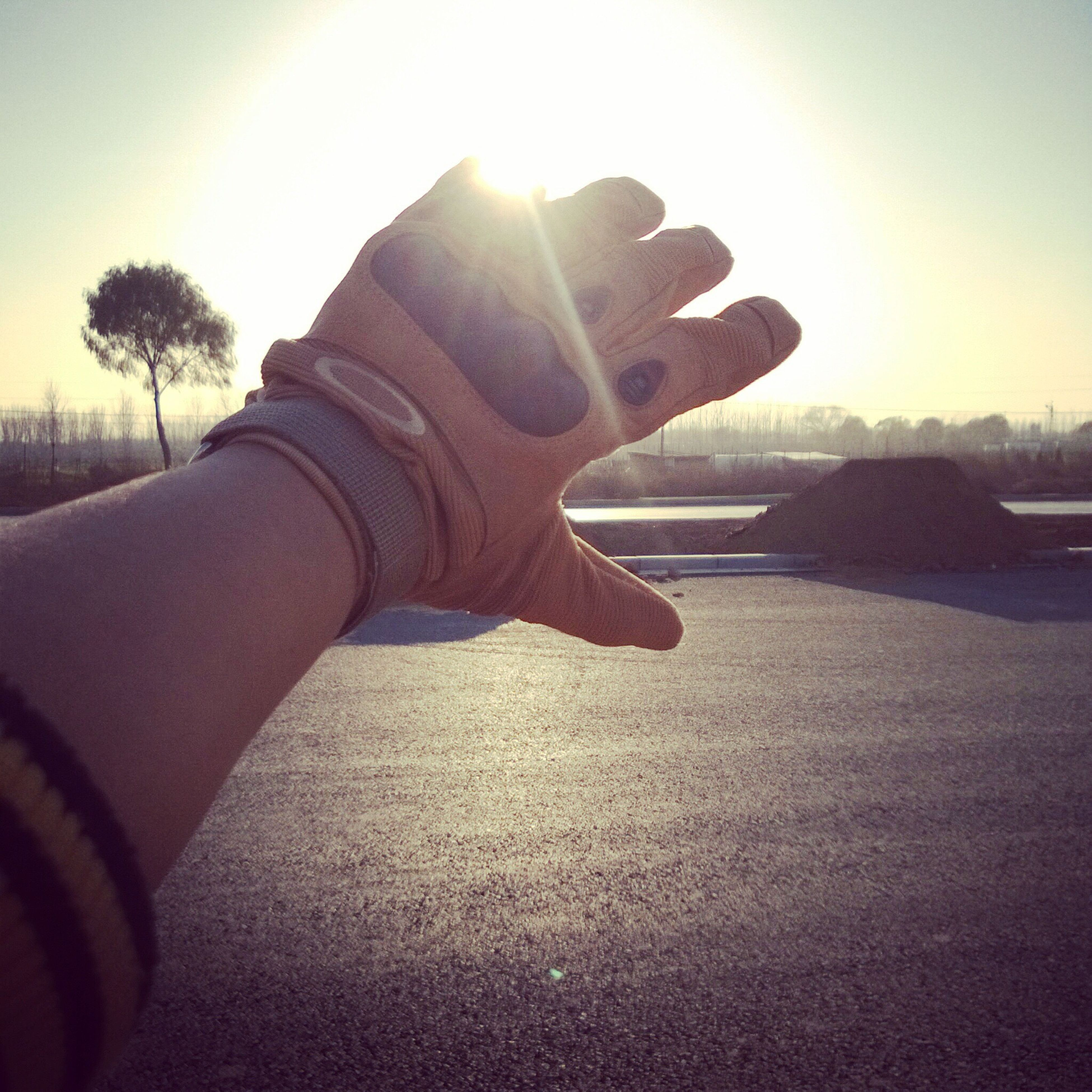sun, sunbeam, person, sunlight, lens flare, part of, personal perspective, lifestyles, sunset, leisure activity, sky, unrecognizable person, men, close-up, human finger, holding, cropped