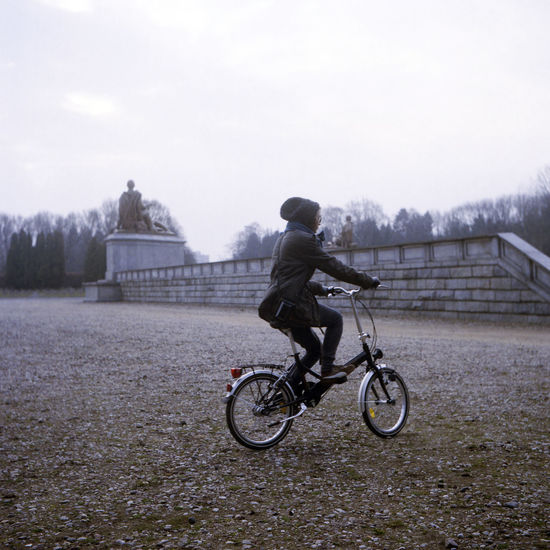 Park alley close to the Soviet Military Cemetery, Warsaw. Soviet Military Cemetery Warsaw Bicycle Cycling Film Photography Filmisnotdead Lifestyles Mausoleum Motion Old Bike One Person Park Riding A Bike  Transportation Vintage Young Adult EyeEmNewHere Shades Of Winter 6x6