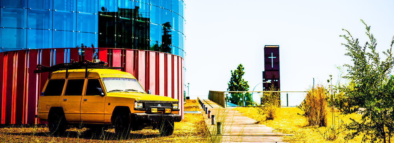 mode of transport, land vehicle, outdoors, transportation, clear sky, yellow, day, building exterior, no people, built structure, industry, architecture, sky, tree