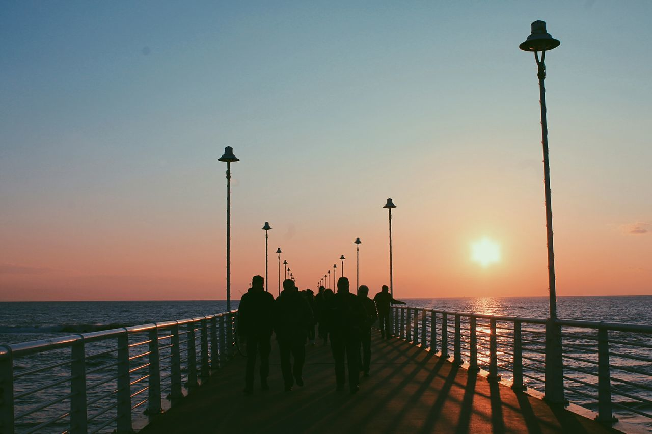 Silhouette People On Pier Against Clear Sky During Sunset