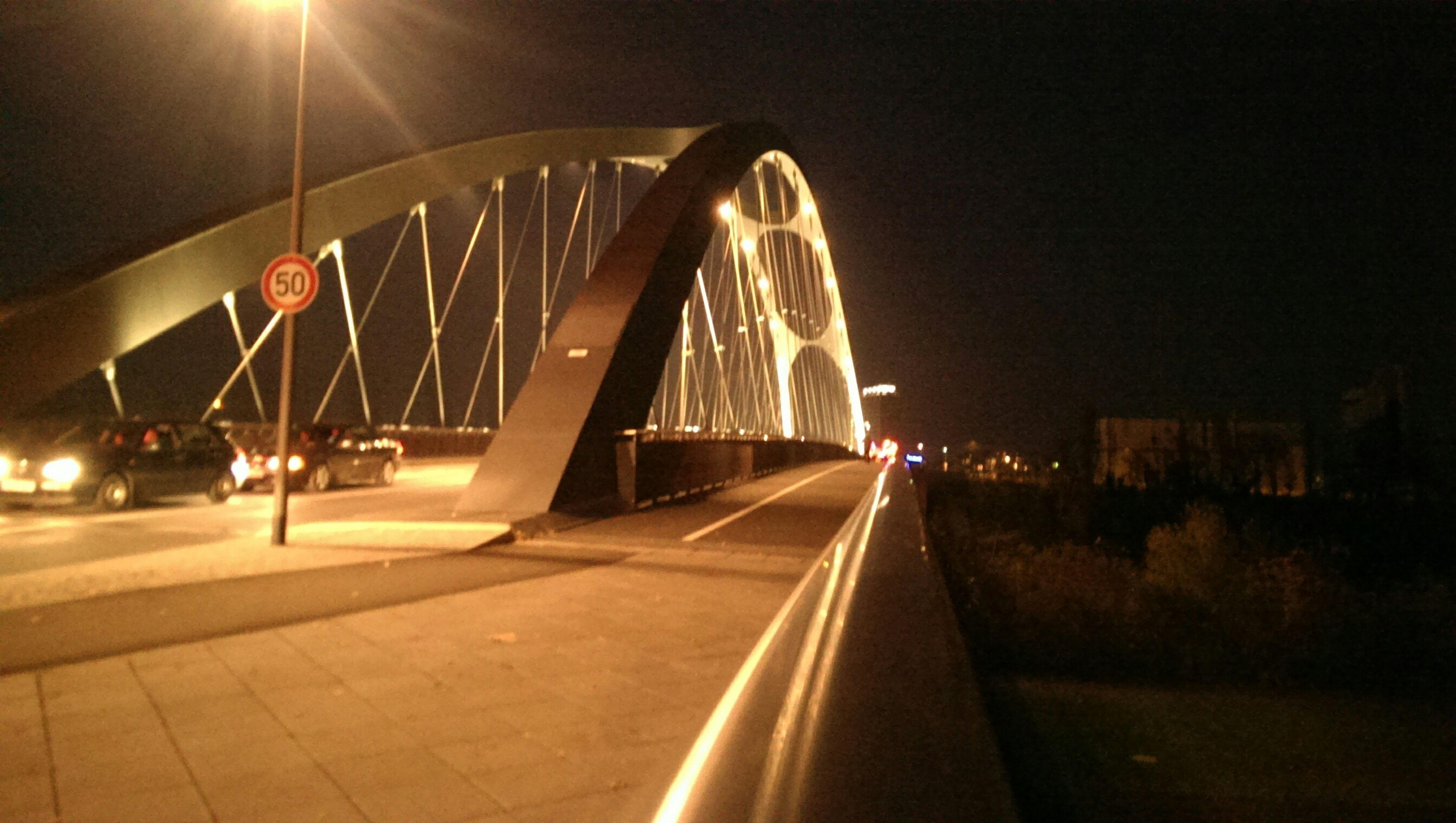 transportation, illuminated, night, the way forward, built structure, architecture, diminishing perspective, metal, vanishing point, bridge - man made structure, connection, engineering, lighting equipment, indoors, railing, travel, mode of transport, incidental people, road, railroad track