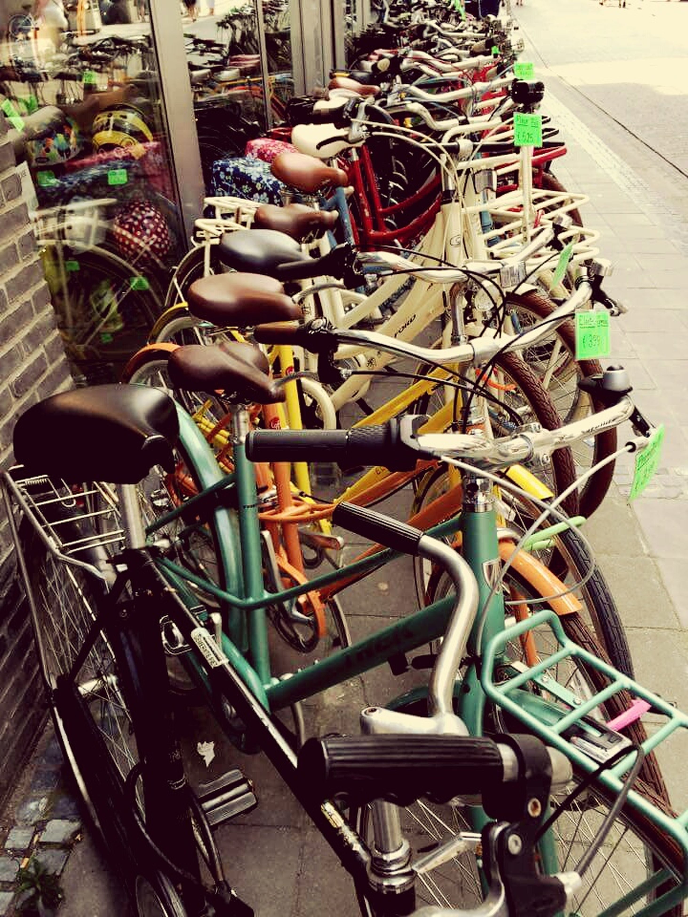 large group of objects, abundance, in a row, bicycle, high angle view, arrangement, metal, variation, parking, transportation, indoors, land vehicle, stationary, hanging, no people, chair, day, order, still life, retail