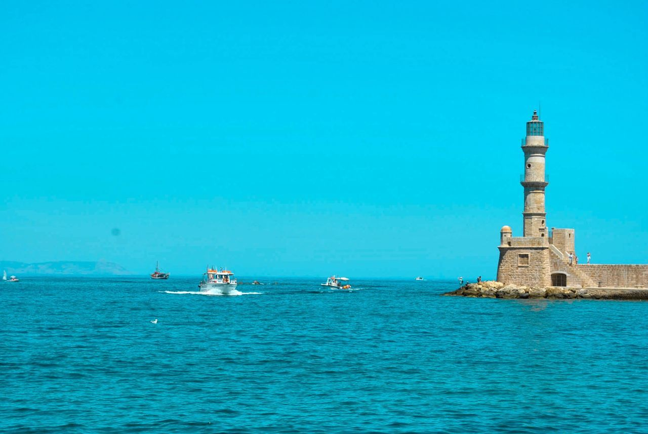 water, blue, sea, day, outdoors, nautical vessel, waterfront, transportation, built structure, beauty in nature, lighthouse, no people, tranquility, architecture, nature, building exterior, clear sky, sky