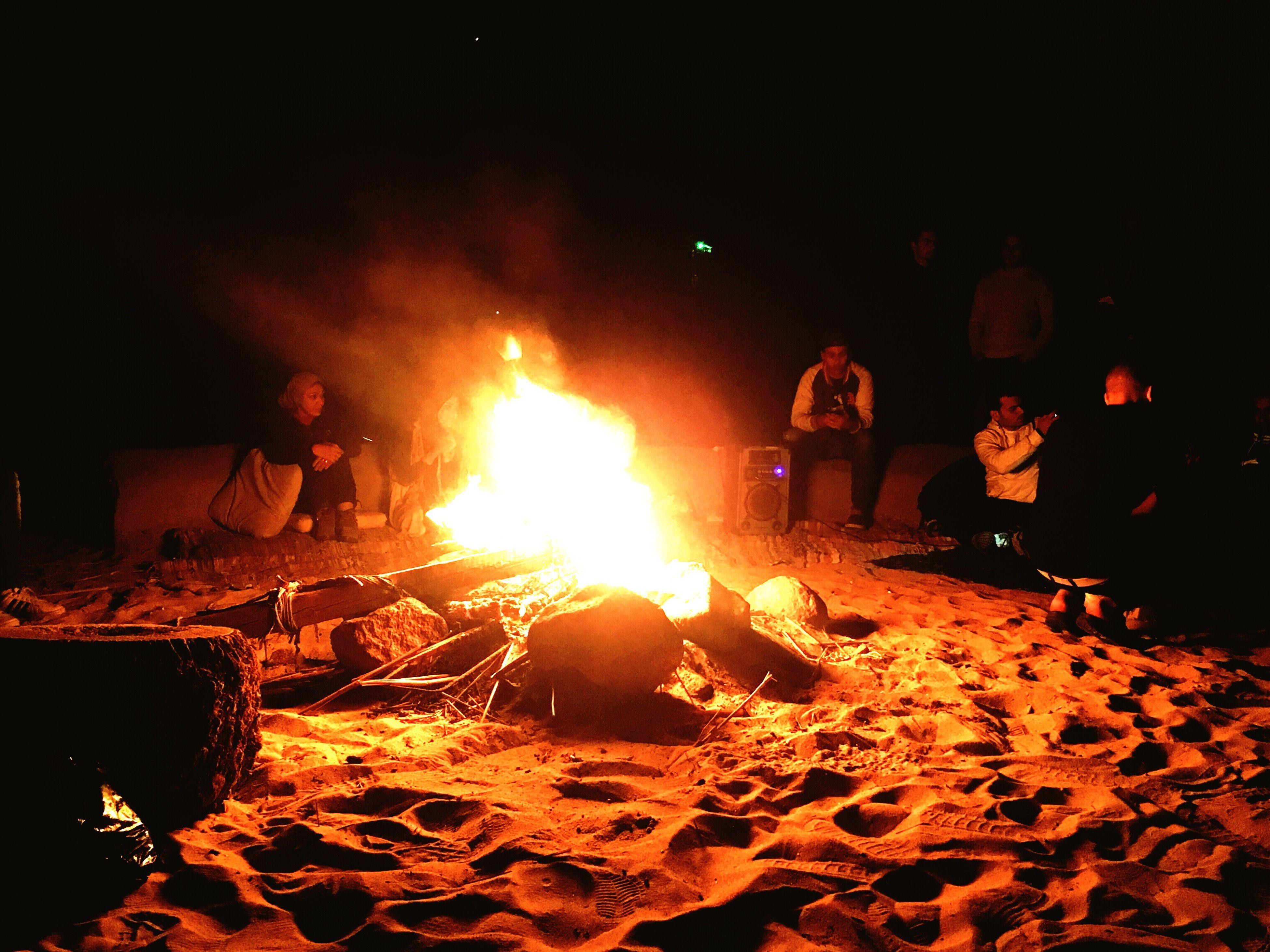 heat - temperature, burning, flame, night, real people, bonfire, men, outdoors, metal industry, people