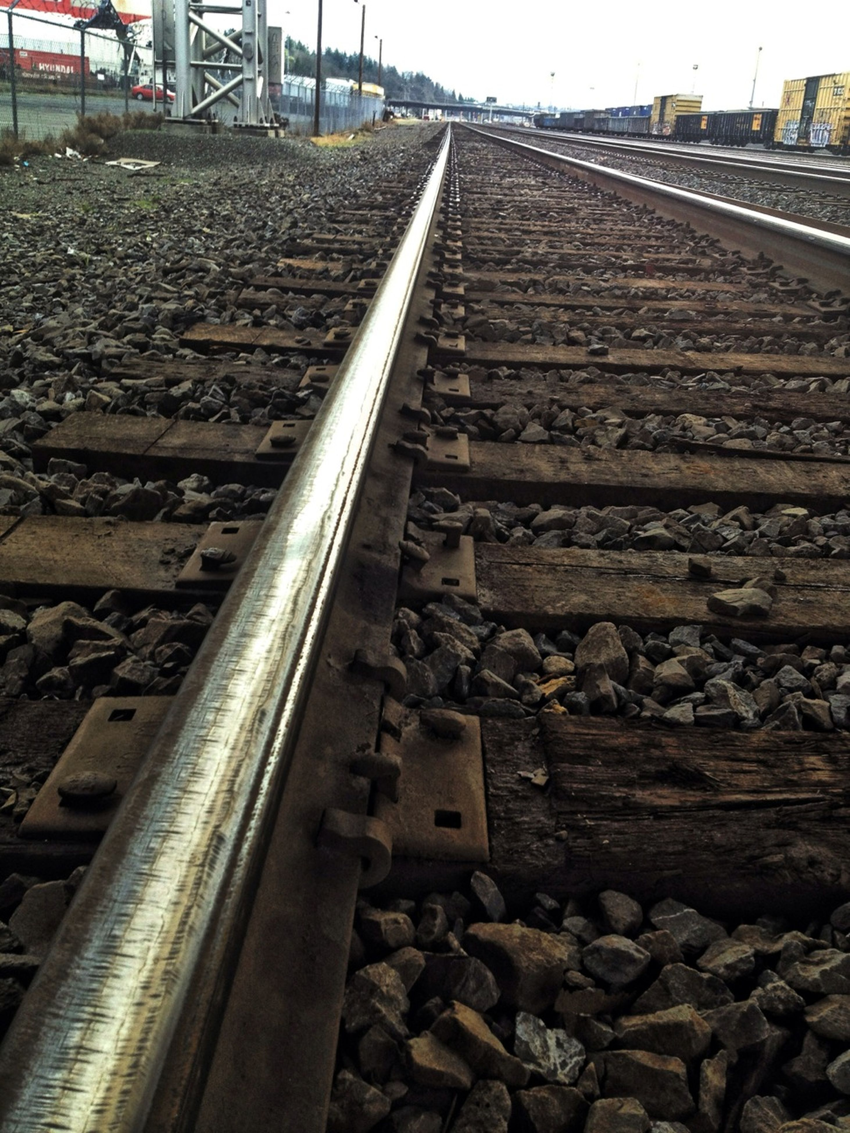 railroad track, the way forward, diminishing perspective, built structure, rail transportation, stone - object, architecture, vanishing point, surface level, metal, gravel, day, outdoors, wood - material, transportation, no people, building exterior, stone, steps, railing