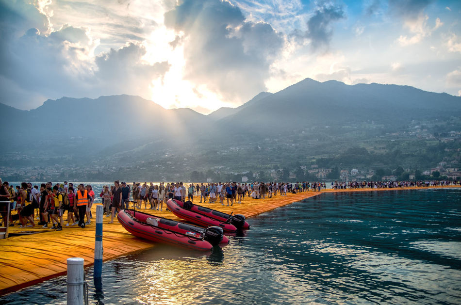Dawn on Christo's Floating Piers Beauty In Nature Cloud - Sky Dawn Of A New Day Day Floating Piers Large Group Of People Moored Mountain Mountain Range Nature Nautical Vessel Outdoors People Real People Scenics Sea Sky Sunlight Sunset Tranquility Transportation Travel Destinations Water Waterfront