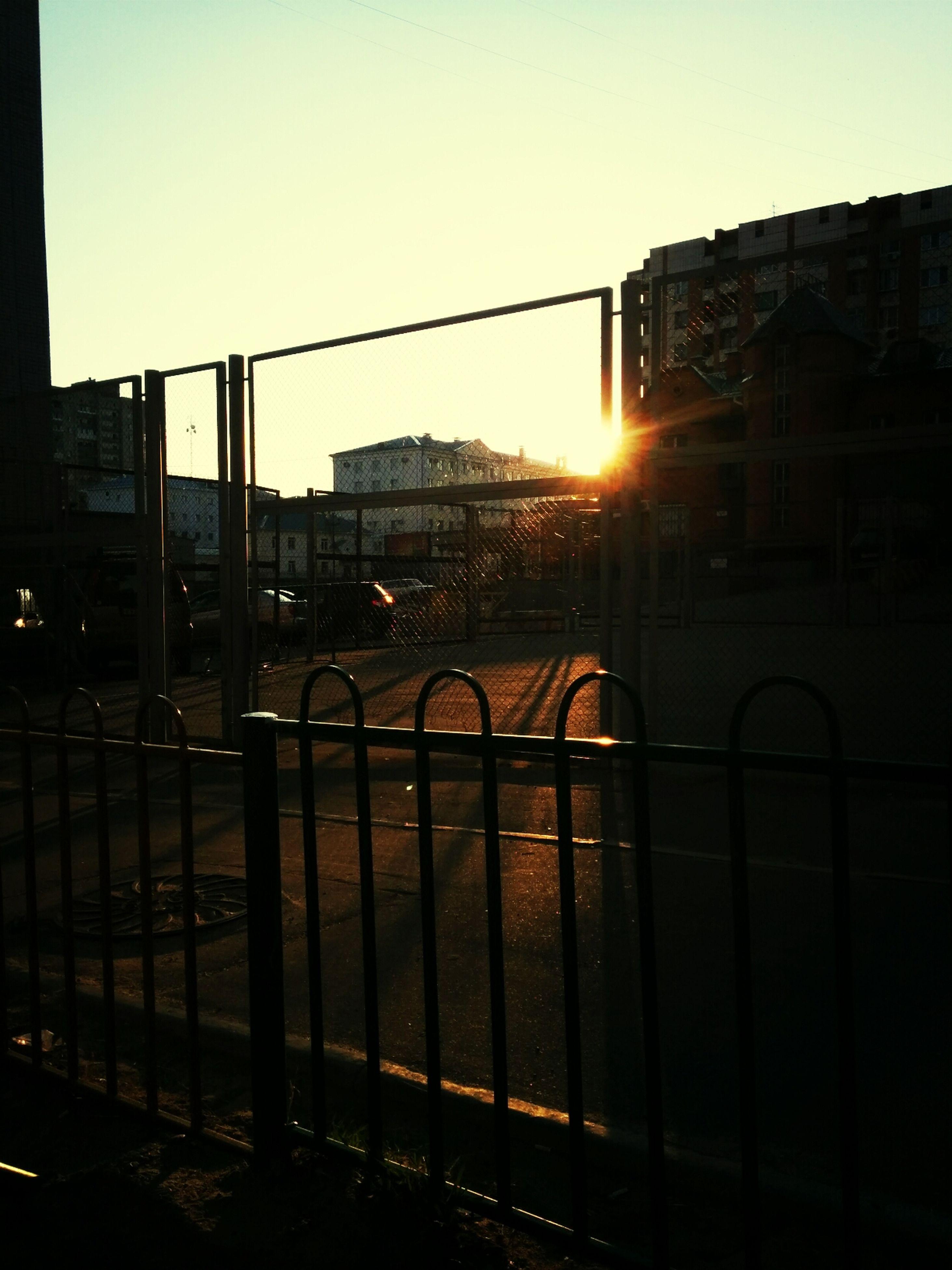 sunset, architecture, building exterior, built structure, sun, city, sunlight, silhouette, sky, building, railing, clear sky, orange color, transportation, sunbeam, lens flare, no people, railroad track, outdoors, street light