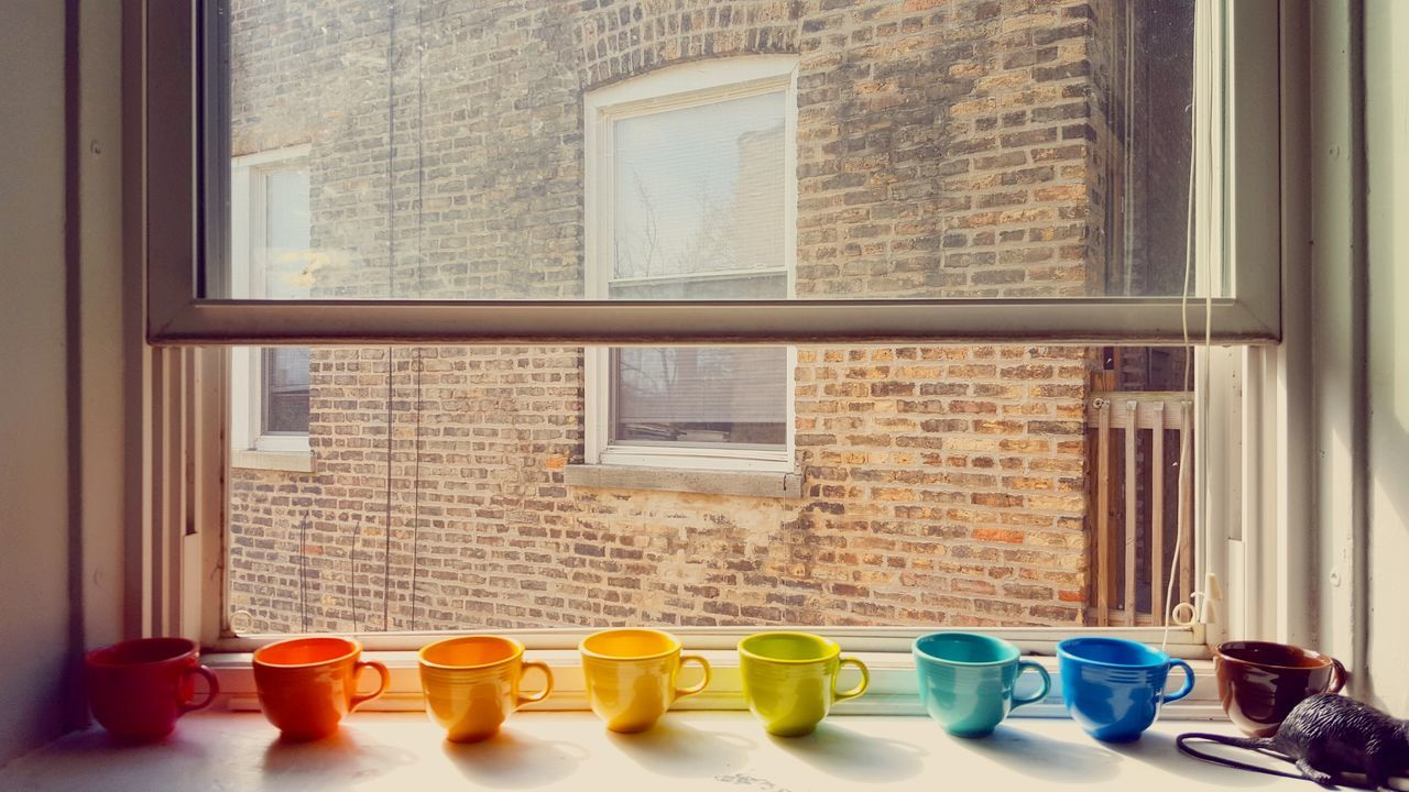 Colorful Mugs On Window Sill In Apartment