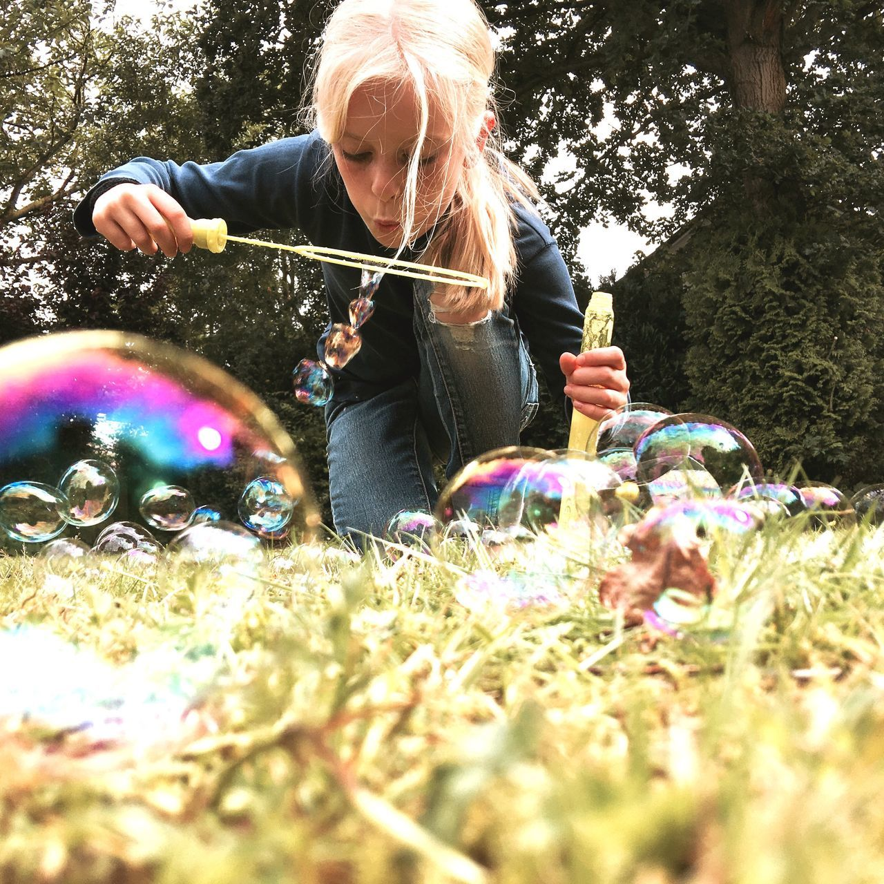 Girl Blowing Bubbles From Wand At Park