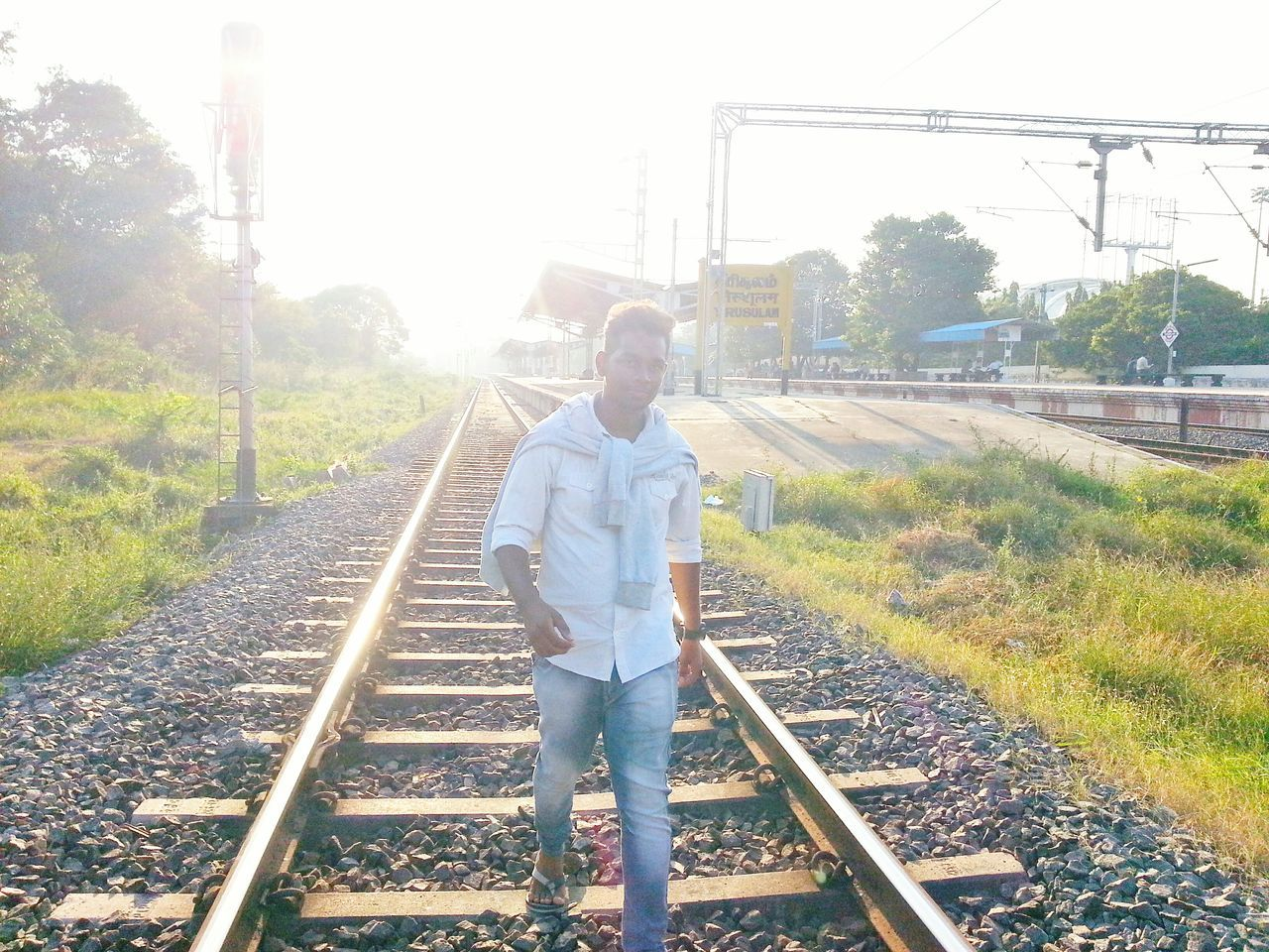 Railroad Track Full Length Rail Transportation One Person Outdoors The Way Forward Sunlight Scenics Green Green Green!  Check This Out! I Show The World What I See Sun_collection Sunset_collection EyeEm Best Shots Freshness Urban Photography Embrace Urban Life Shirts Of EyeEm Jeans Modeling Shoot Model Photography Mensfashion