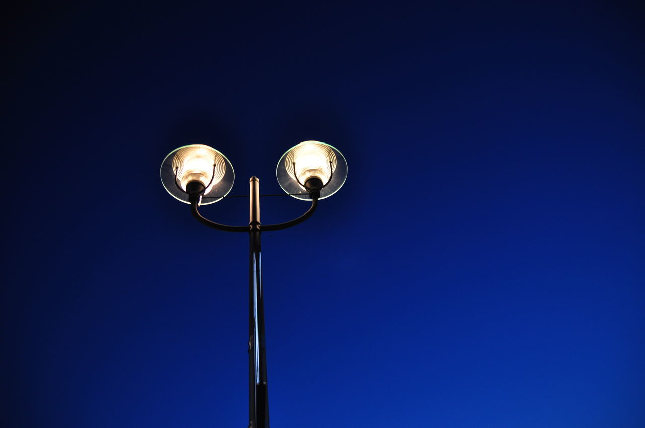 copy space, low angle view, lighting equipment, blue, illuminated, electricity, clear sky, no people, outdoors, night, sky