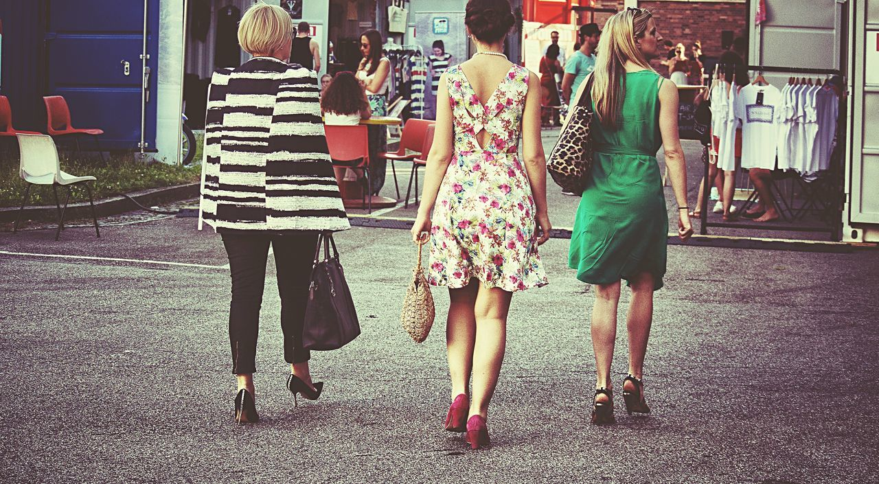 rear view, togetherness, casual clothing, leisure activity, real people, two people, women, friendship, walking, bonding, full length, lifestyles, day, city life, standing, outdoors, city, young women, young adult, adult, people, adults only