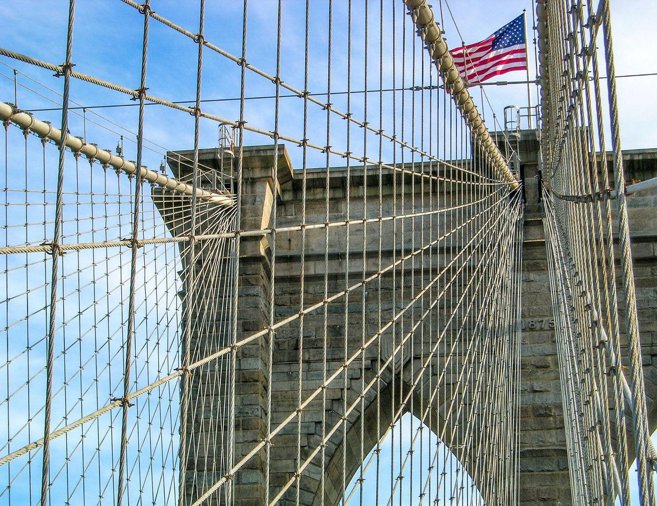 Low Angle View Of American Flag Waving On Brooklyn Bridge