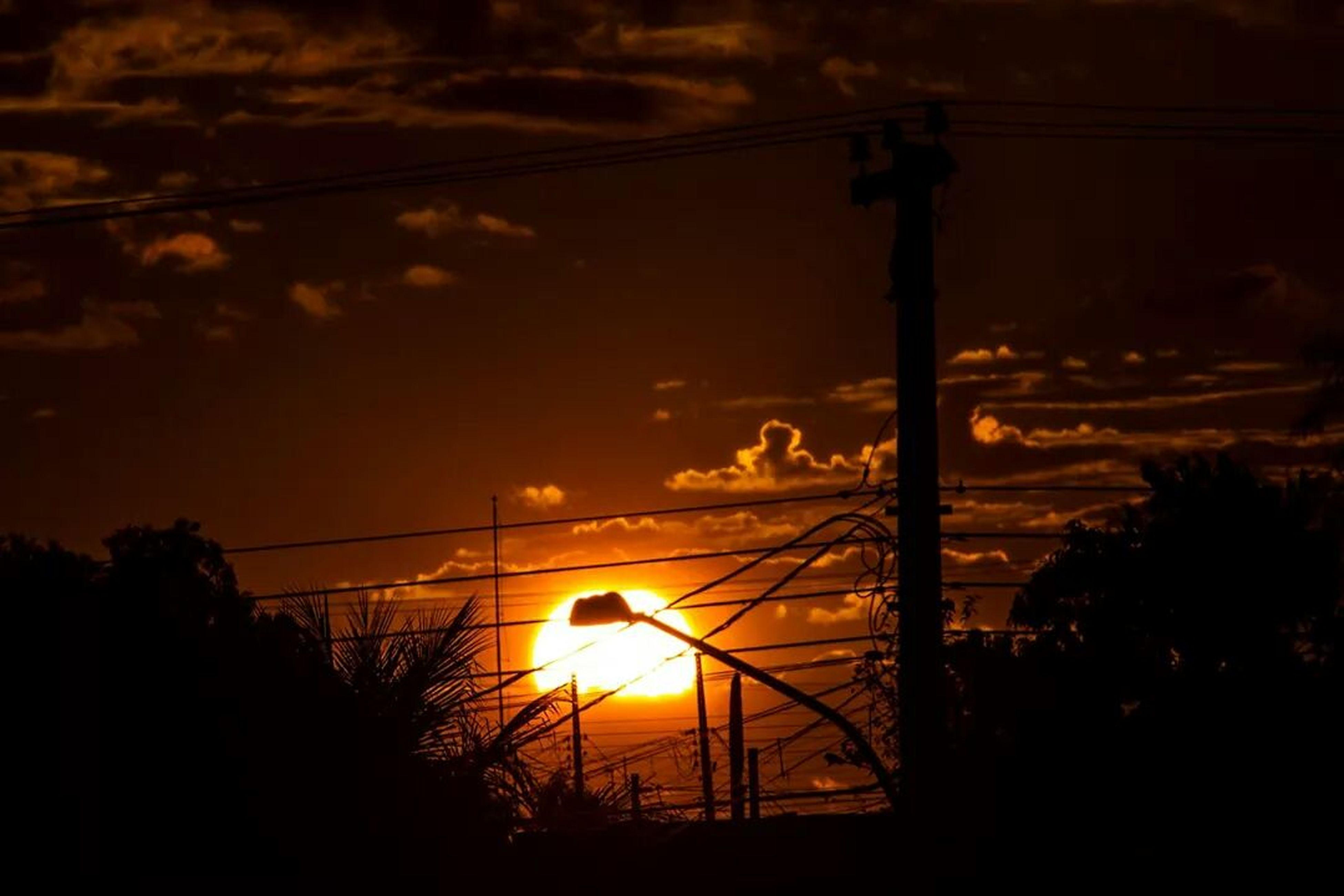 sunset, silhouette, sky, sun, orange color, electricity, power line, tree, street light, low angle view, electricity pylon, dark, cloud - sky, nature, power supply, lighting equipment, sunlight, no people, outdoors, built structure
