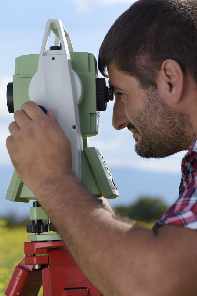 Land surveyor looking through total station. Measurements Industry Plan Scale  Beard Caucasian Coordinate Engineer Equipment Geodesy Keyboard Land Surveying Land Surveyor Location Looking Measurement One Man Only Outdoors Point Pole Position Professional Occupation Stakeout Technology Total Station Wireless Technology
