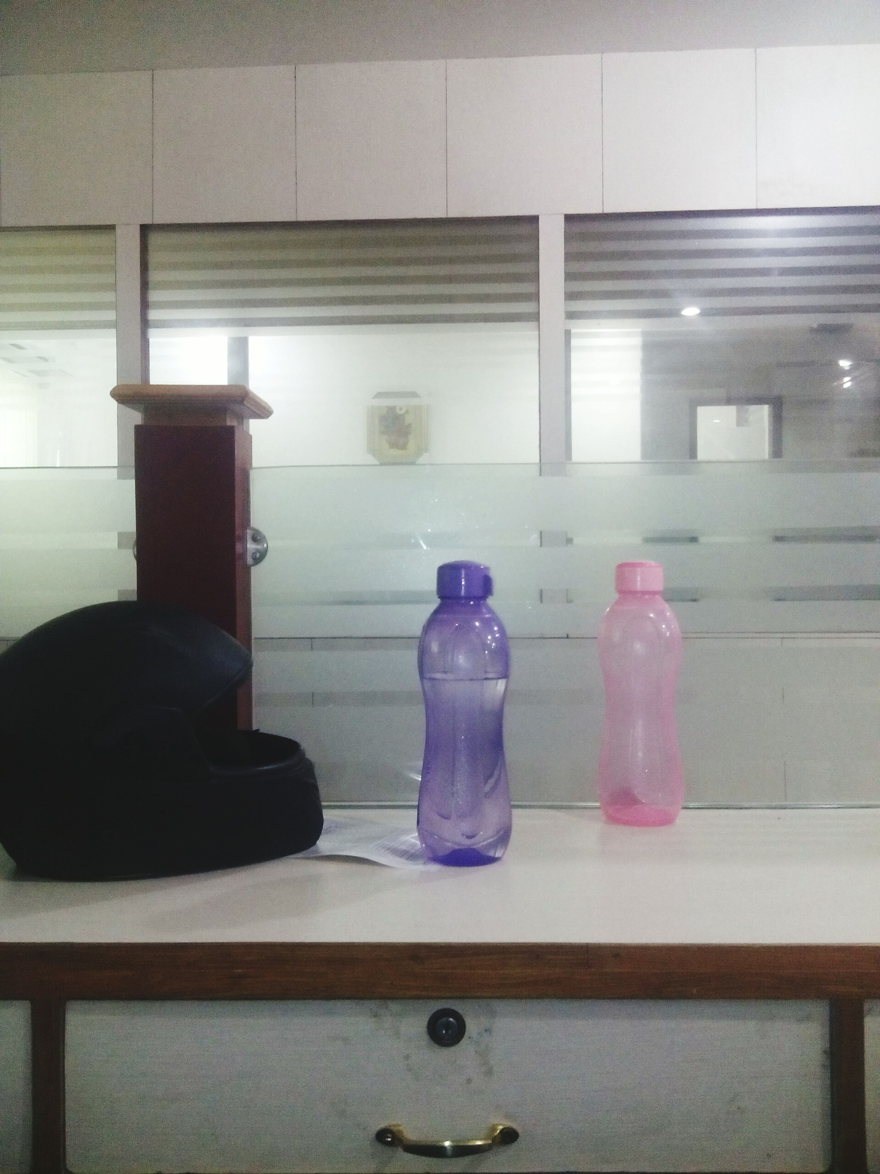 indoors, table, home interior, glass - material, still life, reflection, bottle, wall - building feature, illuminated, lighting equipment, domestic room, transparent, vase, window, no people, absence, chair, wall, flooring, empty