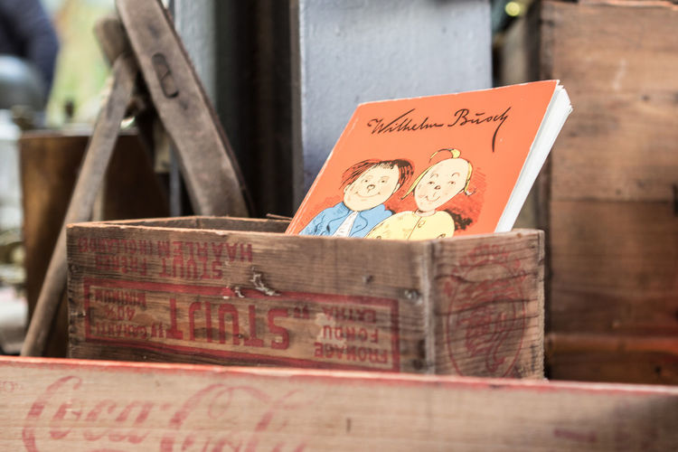 classic German book in a wooden box Orange Typography Wilhelm Busch Book Classic Books Coca Cola Colour Day Fleamarket Marketplace No People Text Wooden Box