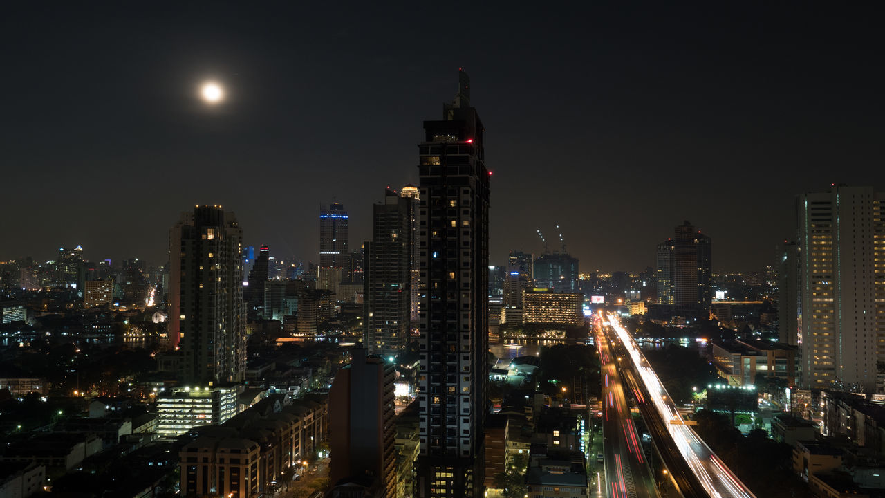 Bangkok panorama at night. View to the illuminated high-rise buildings and skyscrapers with transport traffic on highway. Capital of Thailand Architecture ASIA Bangkok Car City Cityscape Highrise Horizontal Illuminated Modern Moon Moon Night No People Outdoors Panorama Road Urban Urban Skyline View