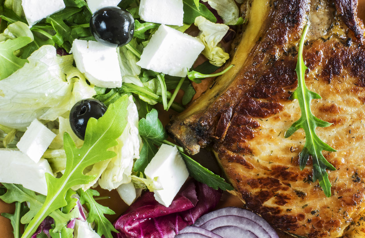 Roasted pork chop on a plate with a green salad, red onion, soft cheese and olives Cheese Chop Food Food And Drink Freshness Green Green Color Healthy Eating Indoors  Leaf Leaf Vegetable Lettuce Meal Meat No People Olives Onion Plate Pork Relaxing Roasted Salad Salad Soft Vegetable