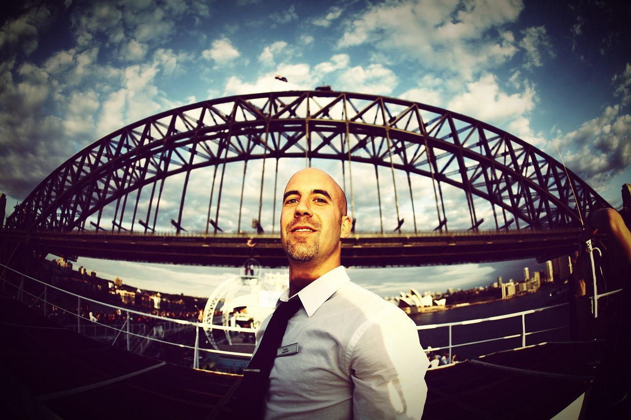 Portrait Of Businessman Standing In Ship Against Sydney Harbor Bridge