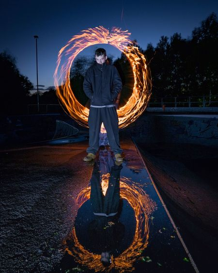 Night Motion Long Exposure Illuminated Real People Blurred Motion Burning Outdoors Lifestyles One Person Celebration Men Women Full Length Sparkler Standing Performance Wire Wool Tree Sky