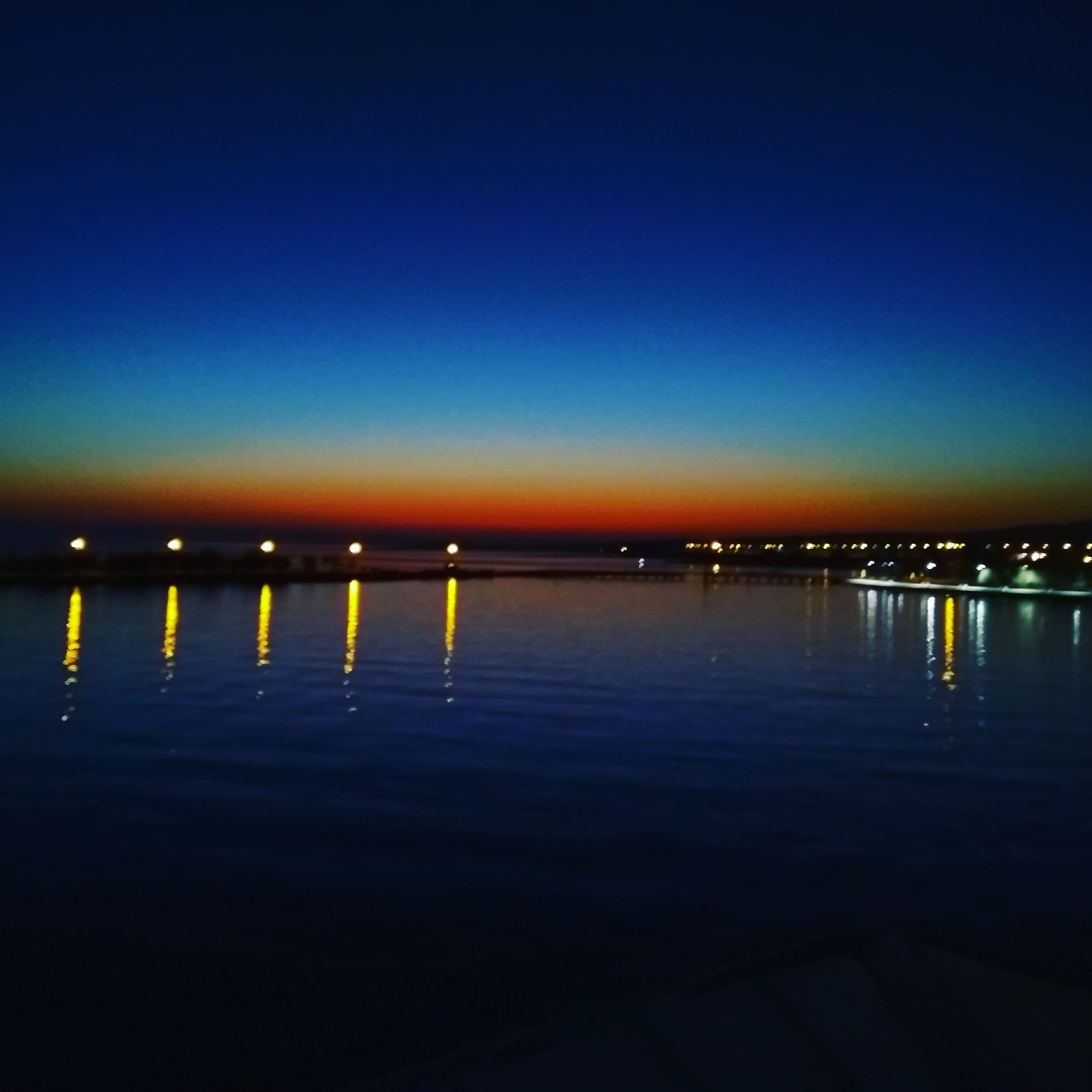 water, blue, reflection, night, no people, outdoors, illuminated, tranquility, waterfront, nature, sunset, clear sky, scenics, beauty in nature, architecture, sea, sky