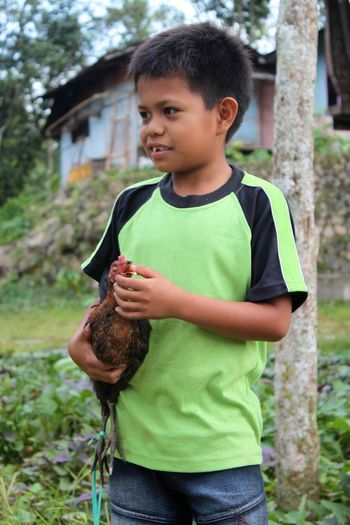 INDONESIA Sulawesi Tana Toraja Boys Casual Clothing Childhood Elementary Age Green Color Growth Happiness Holding Lifestyles Nature One Boy Only One Person Outdoors Portrait Real People Standing Toy