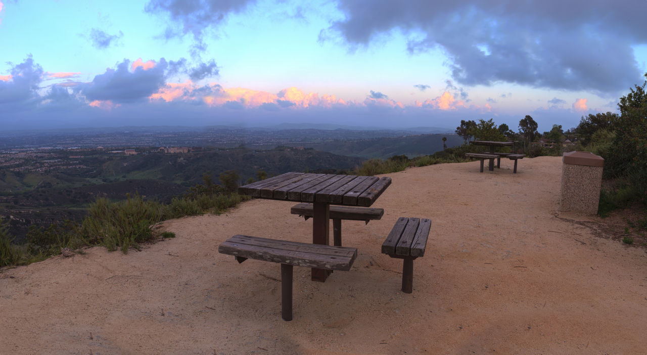 Panoramic view before sunset from the top of the hiking trail at Alta Laguna Park, Top of the World, overlooking the picnic benches and saddleback mountains in Laguna Beach, Southern California Chair Day Hiking Trail Journey Laguna Beach, CA Mountain View Nature No People Outdoors Pathway Picnic Table Sky And Clouds Sunset Top Of The World Travel