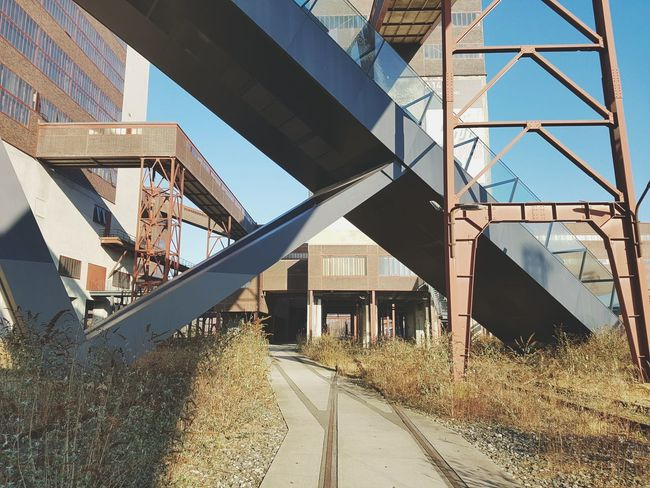 Lines Bridge - Man Made Structure Steel Modern Architecture Below No People Elevated Walkway Lines Old Buildings Adapted To The City Rusty Factory Facades Steelwork Abandoned Winter Sunlight Vintage Objects Futuristic Architecture Clear Sky Built Structure Walls Shadow The Architect - 2017 EyeEm Awards