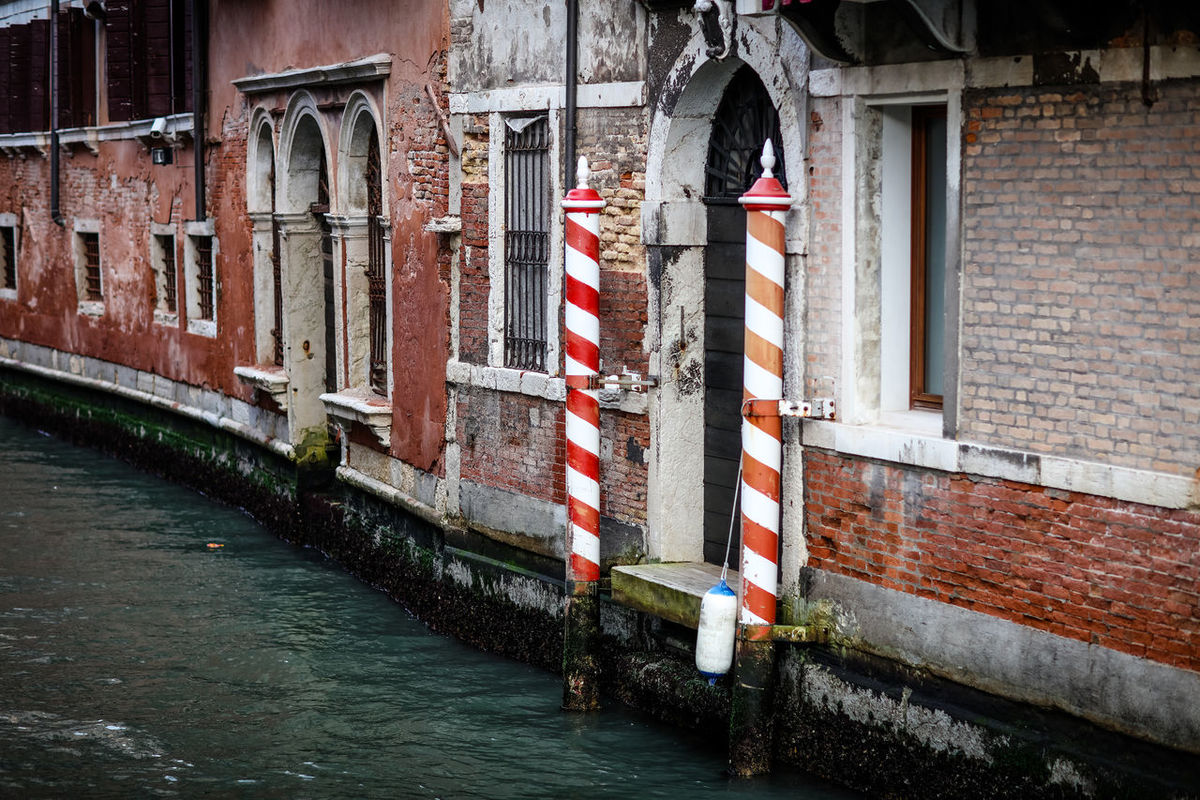 Canal The Week On EyeEm Venice, Italy Water Way Architecture Brick Wall Building Exterior Built Structure Canal Day Mooring Post No People Outdoors Red & White Red Poles Street Street Photography Streetphotography Venice Water