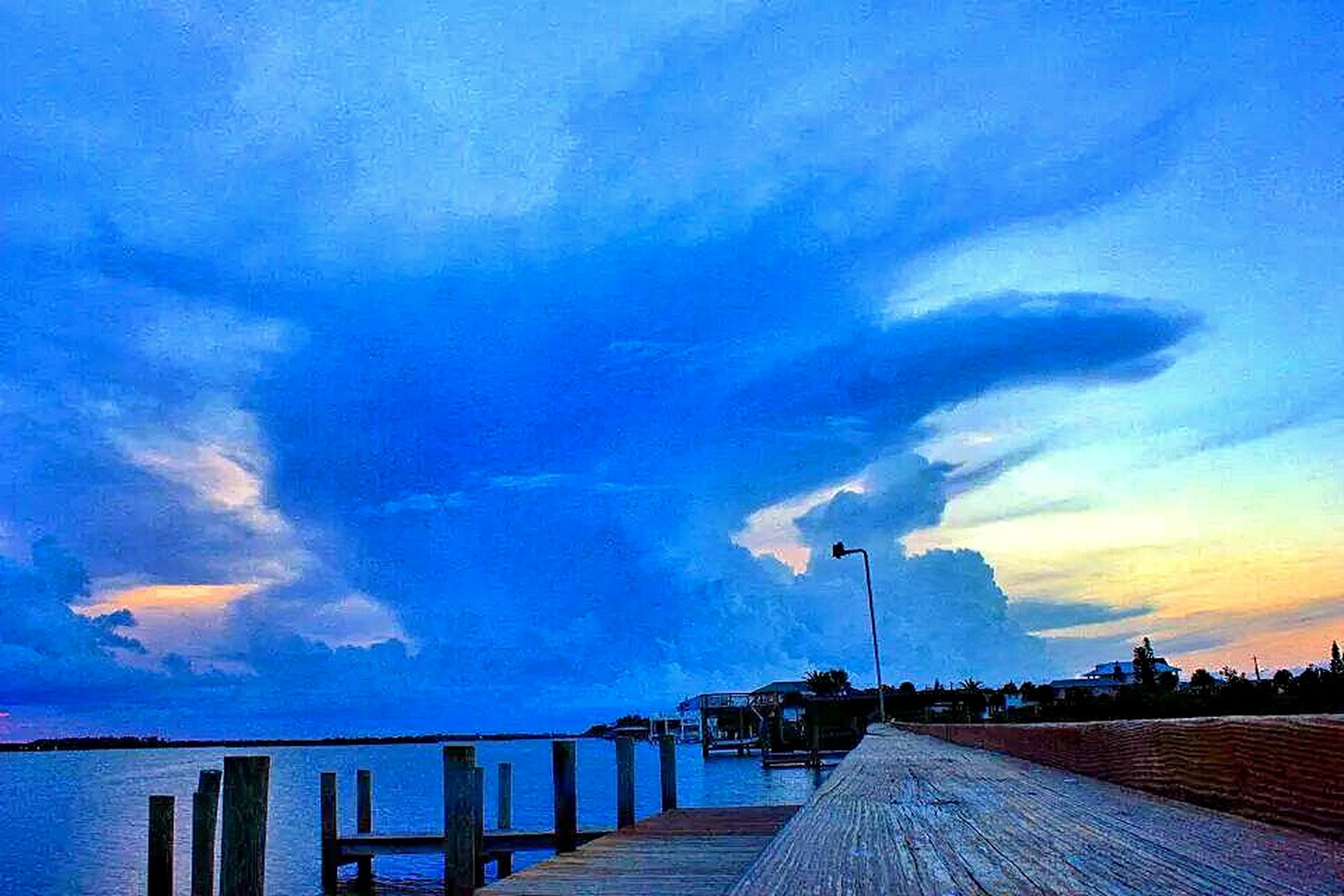 sky, the way forward, cloud - sky, blue, built structure, railing, architecture, cloud, water, diminishing perspective, tranquility, building exterior, sunset, cloudy, nature, scenics, sea, beauty in nature, tranquil scene, pier